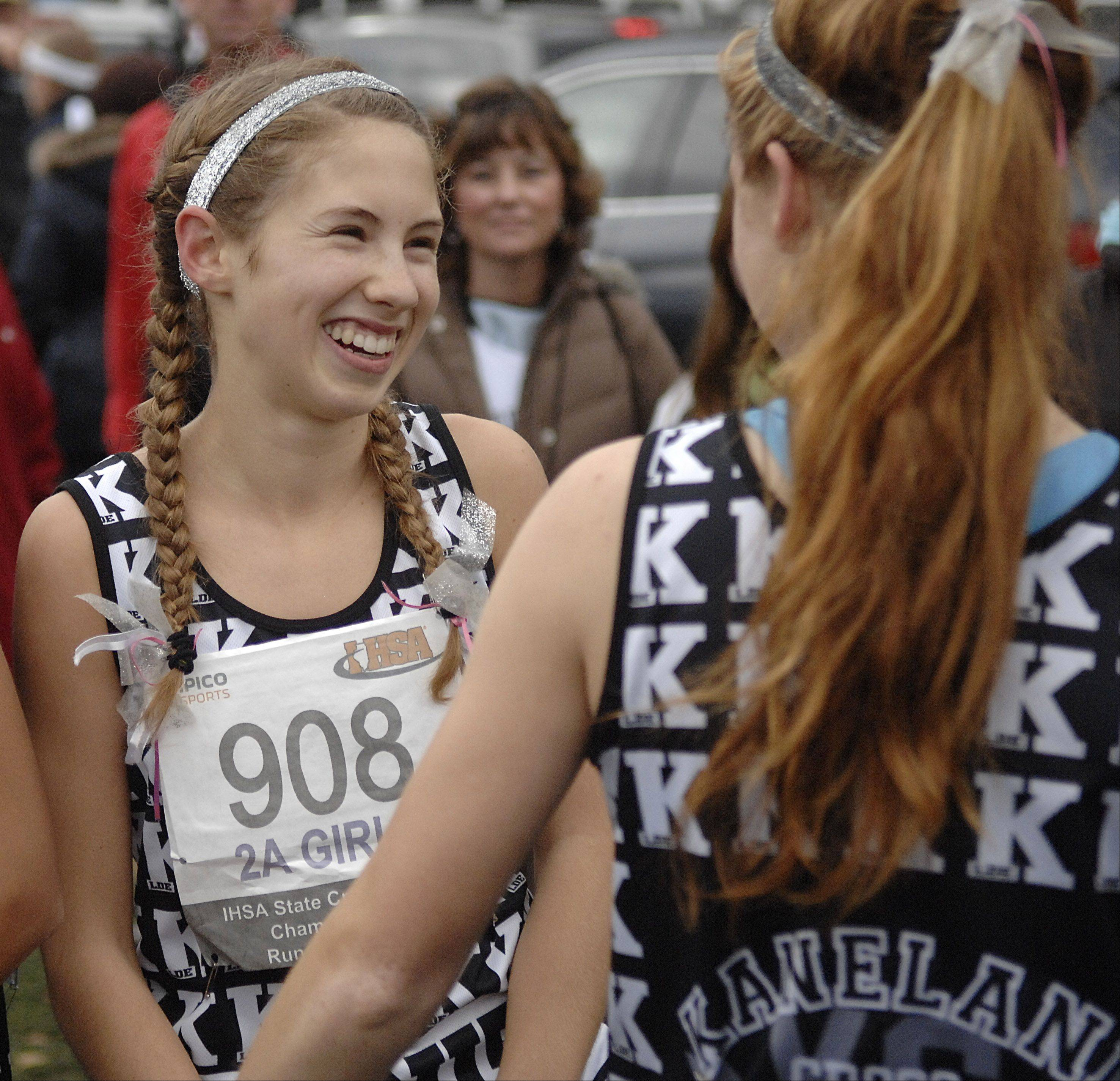 Kaneland's Victoria Clinton is congratulated by teammate Aislinn Losdwig after winning the 2A state cross country final in Peoria on Saturday, November 3.
