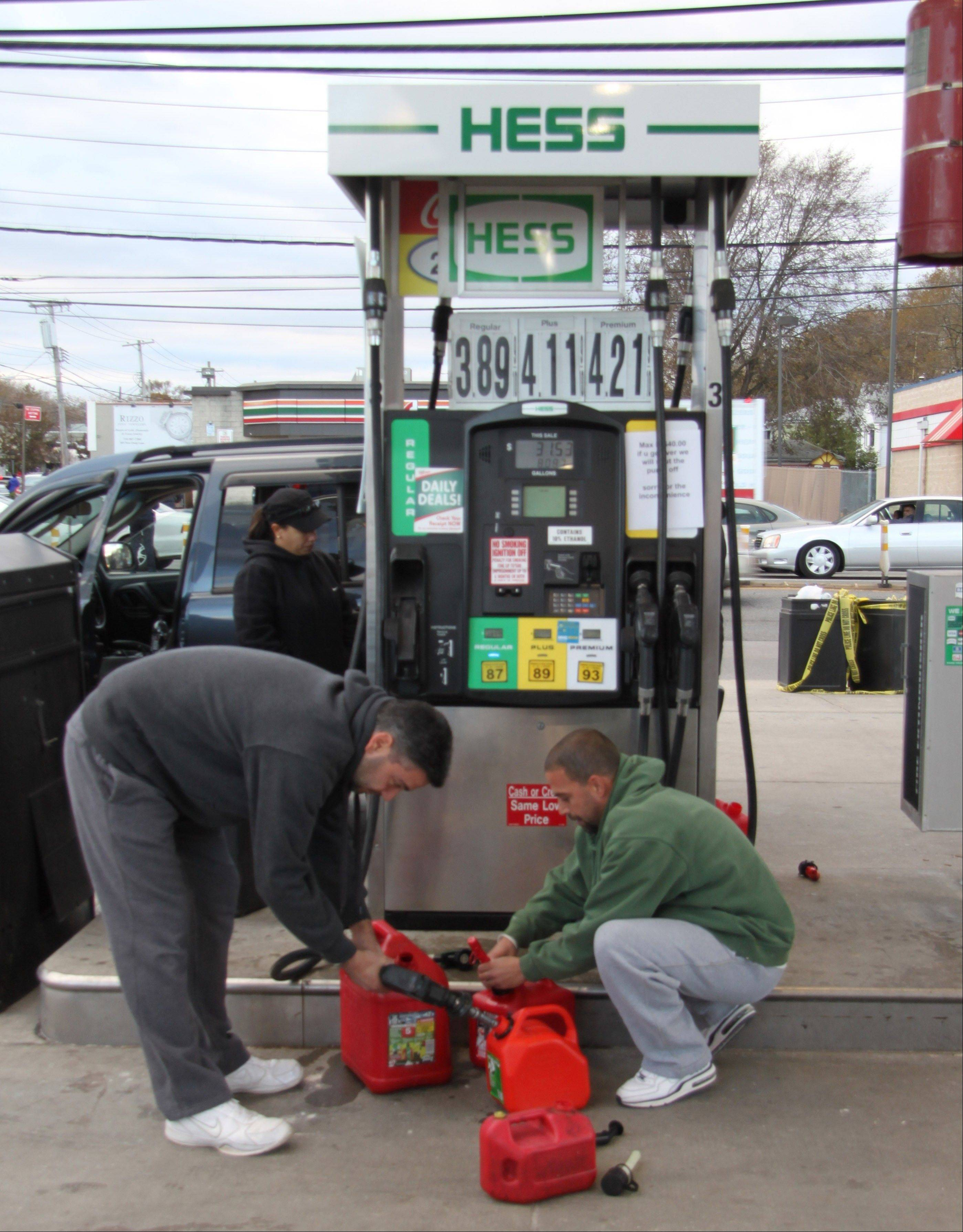 Ross Napoli, left, and Rob Balletto fill gas canisters at a Hess station in the New Dorp section of the Staten Island borough of New York for use in their cars Saturday. They had waited in line for about 40 minutes. The line for cars at the station was much longer, with drivers waiting for up to two hours.
