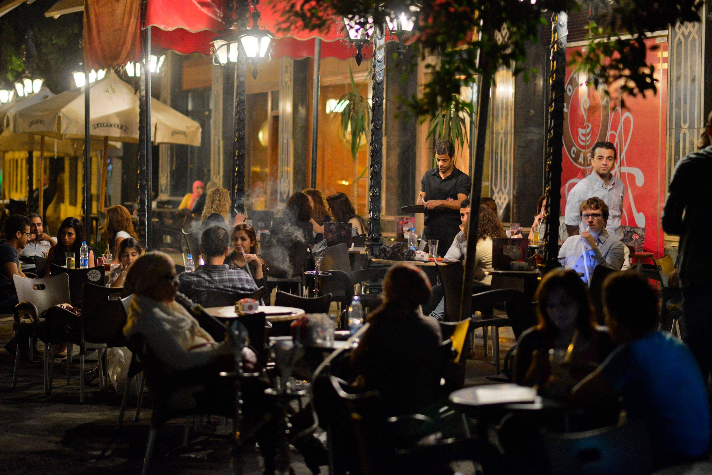 Egyptians relax outside a cafe in Cairo, Egypt Wednesday. Egypt's capital prides itself on being city that never sleeps, with crowds filling cafes and shops open into the small hours. So the government is facing a backlash from businesses and the public as it vows to impose new nationwide rules closing stores and restaurants early. Officials say the crisis-ridden nation has to conserve electricity, but they also seem intent on taming a population they see as too unruly.