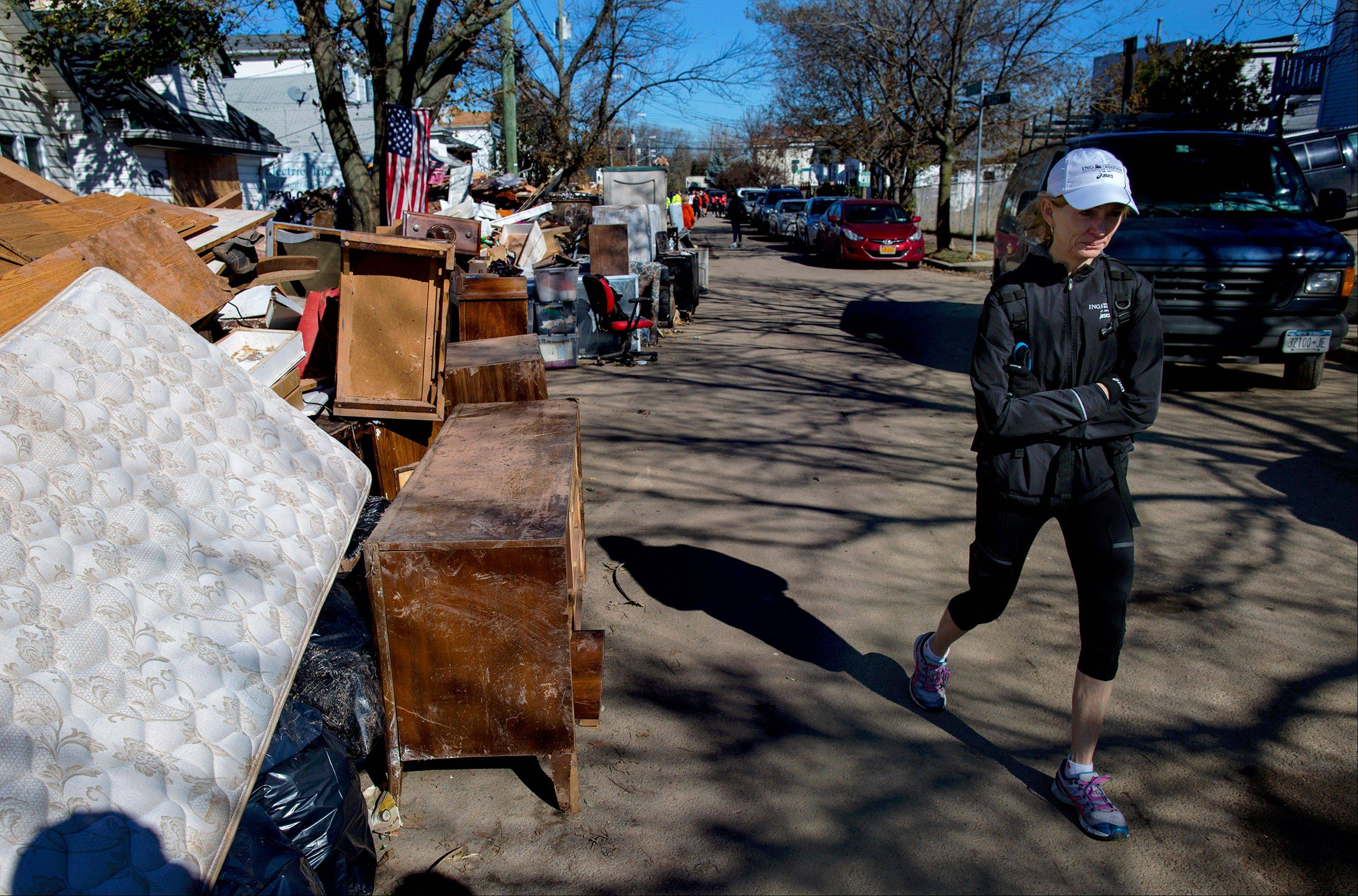 Mary Wittenberg, president of the New York Road Runners, reacts after speaking with a family whose house was heavily damaged during Superstorm Sandy in the Staten Island borough New York ON Sunday.