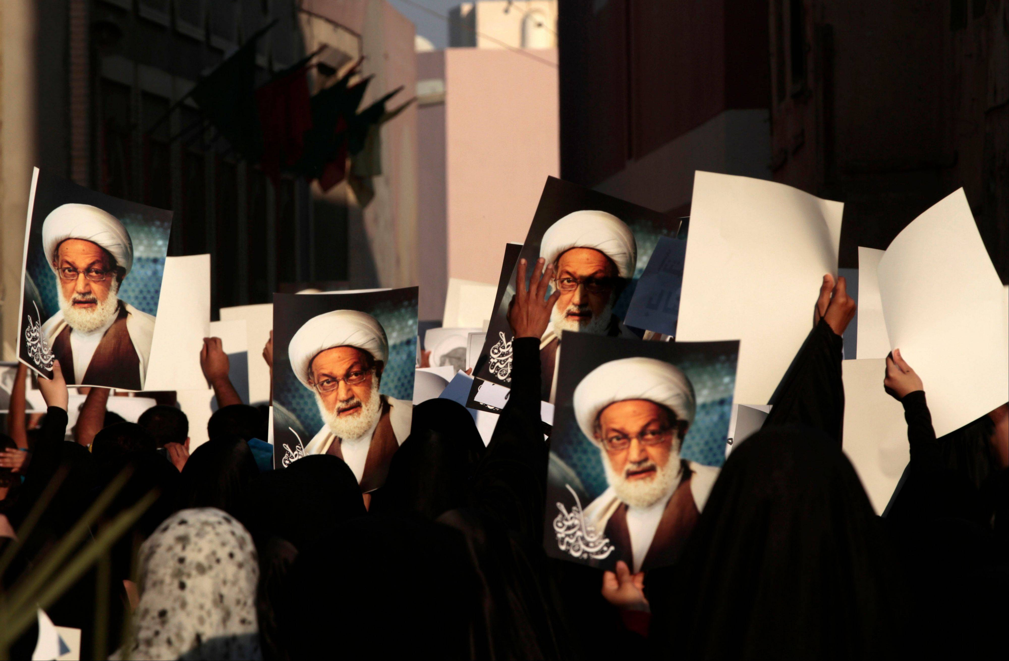 Bahraini anti-government protesters hold pictures of top Shiite cleric Sheik Issa Qassim during a march in Duraz, Bahrain, Friday that demonstrators said was held out of concern Qassim would be arrested. Demonstrations were held in several villages nationwide Friday, challenging a new government ban on protests.