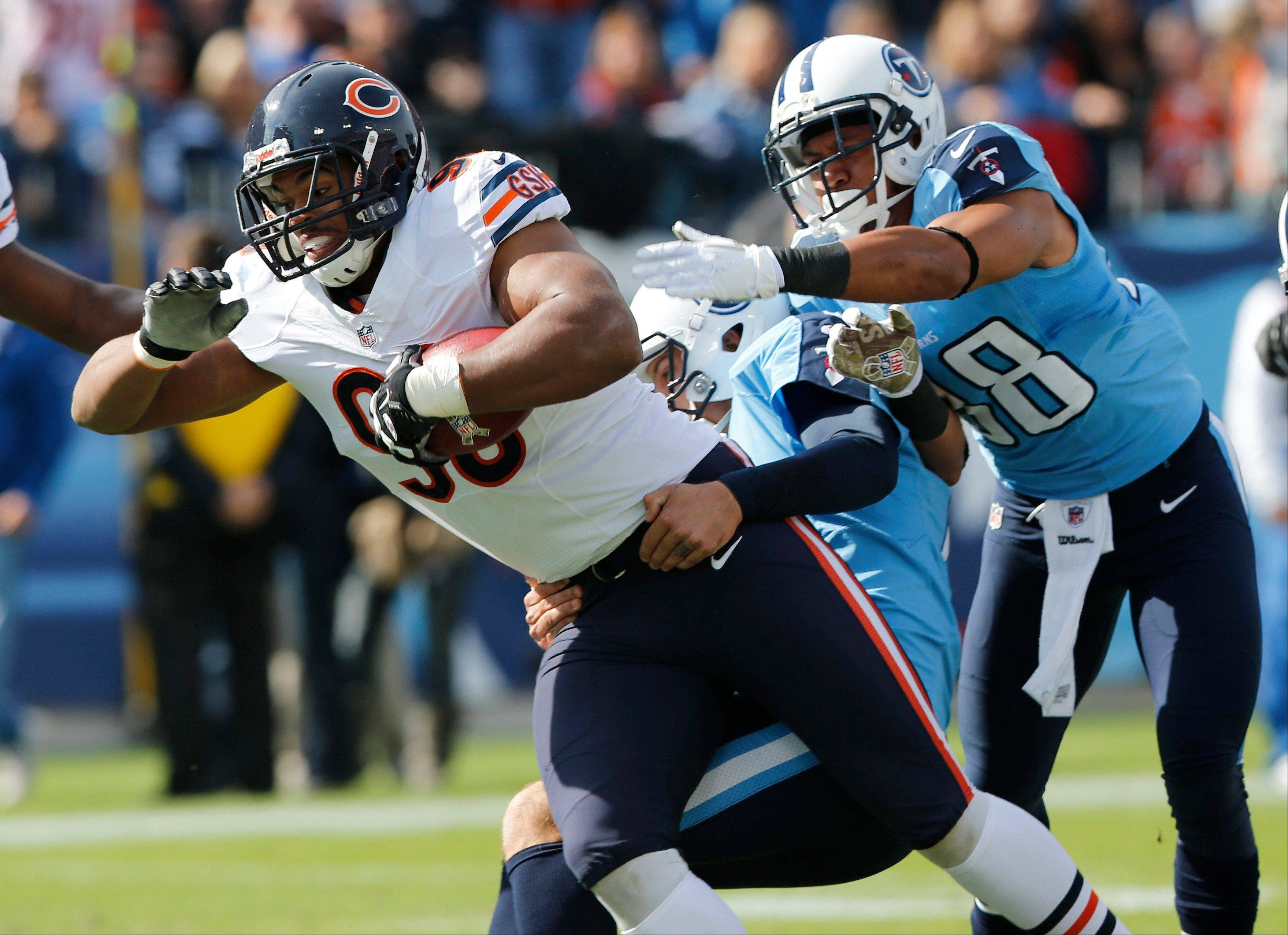 Chicago Bears defensive end Corey Wootton (98) scores a touchdown after he recovered a blocked punt as Tennessee Titans punter Brett Kern, center, and safety Al Afalava (38) try to bring him down in the first quarter of an NFL football game Sunday, Nov. 4, 2012, in Nashville, Tenn.