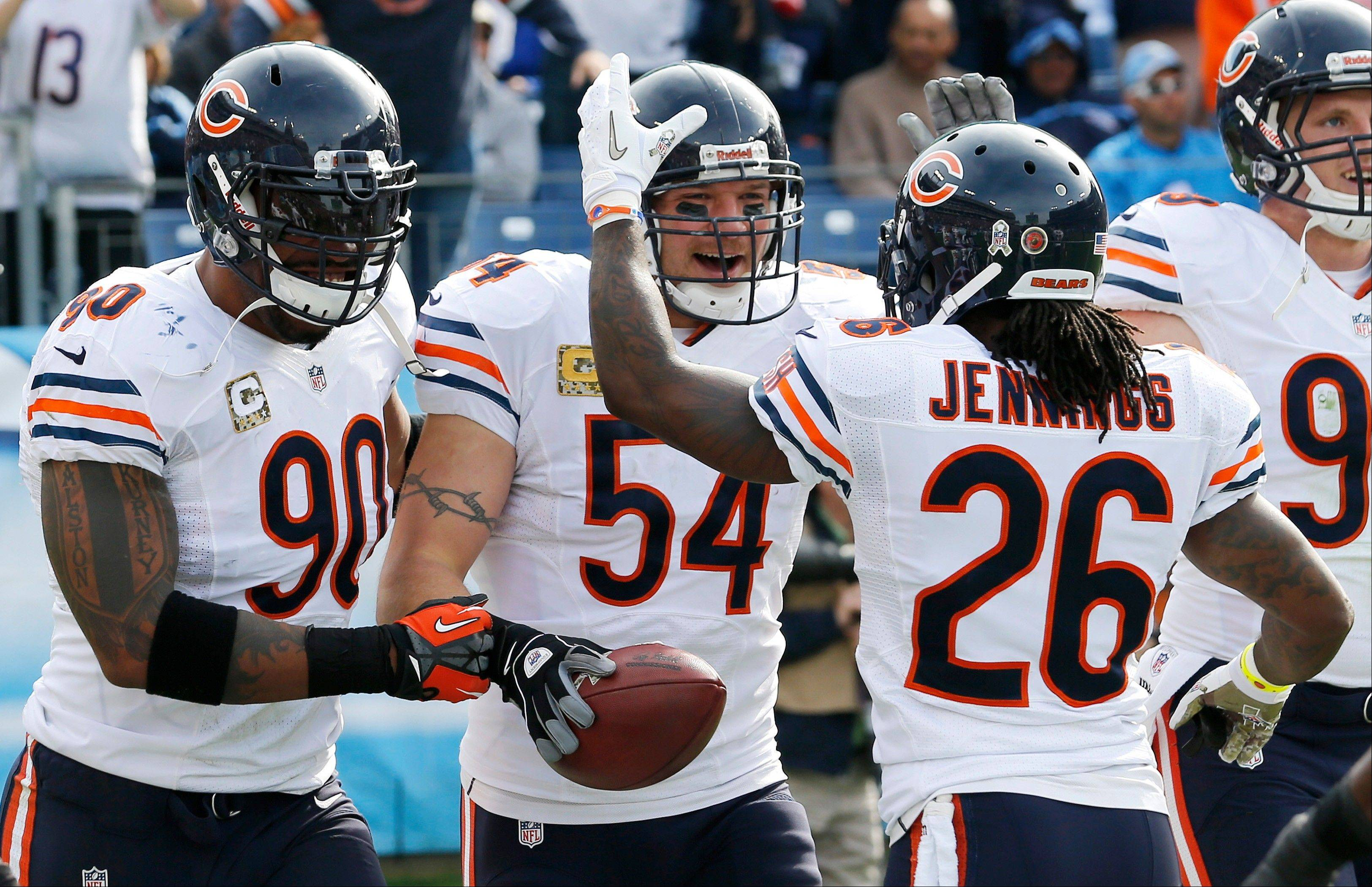 Chicago Bears middle linebacker Brian Urlacher celebrates with Julius Peppers and Tim Jennings after Urlacher returned an interception for a touchdown against the Tennessee Titans in the first quarter of an NFL football game on Sunday, Nov. 4, 2012, in Nashville, Tenn.