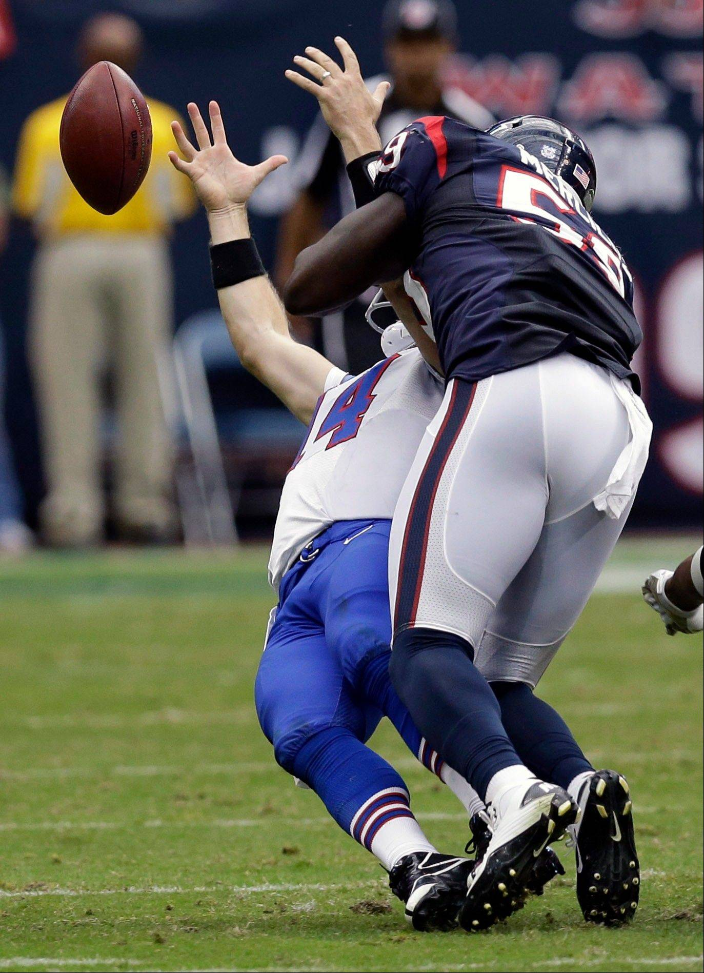 Houston Texans linebacker Whitney Mercilus hits Buffalo Bills quarterback Ryan Fitzpatrick, left, causing a fumble in the fourth quarter Sunday in Houston.