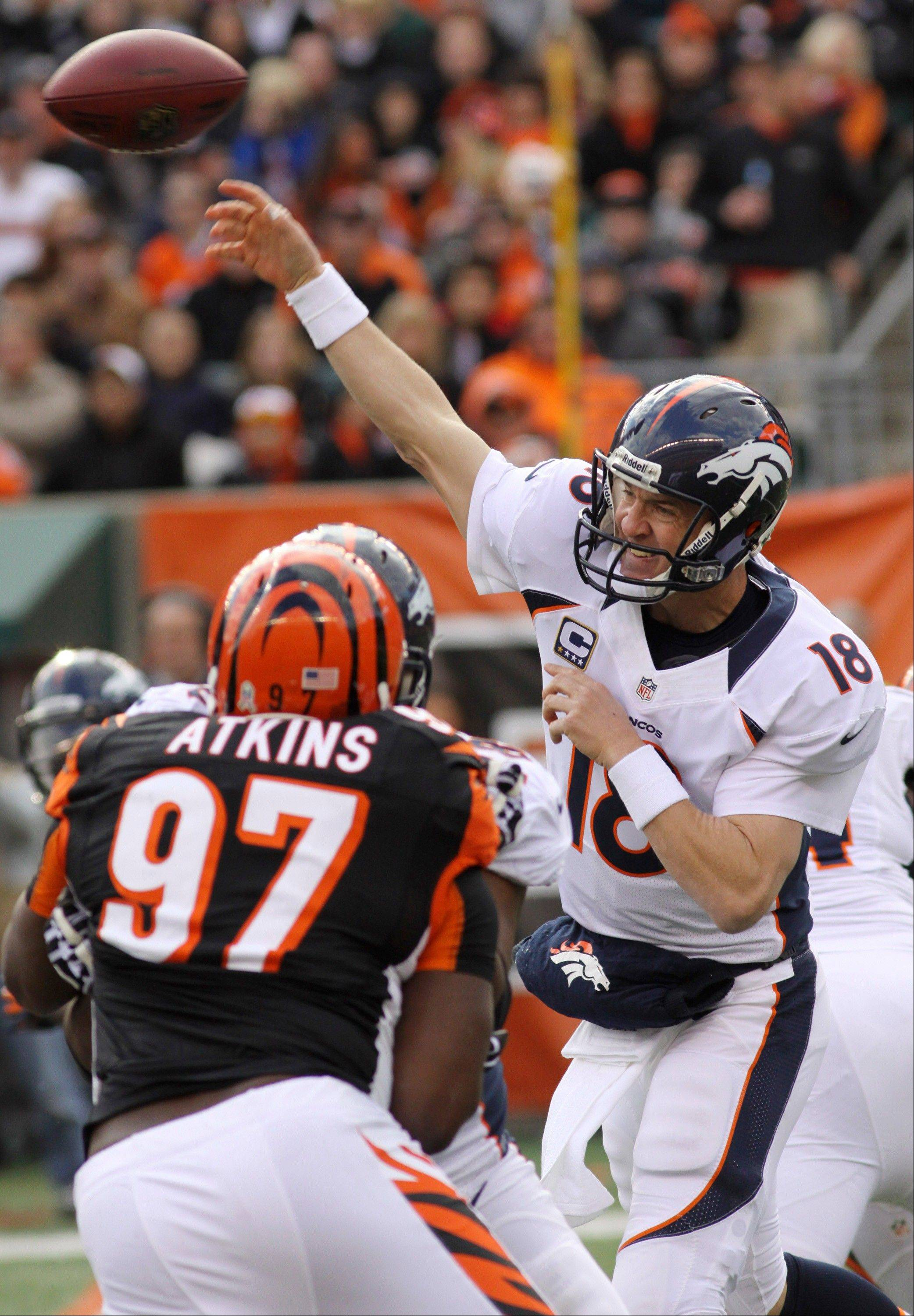 Denver Broncos quarterback Peyton Manning passes under pressure from Cincinnati Bengals defensive tackle Geno Atkins in the second half Sunday in Cincinnati.