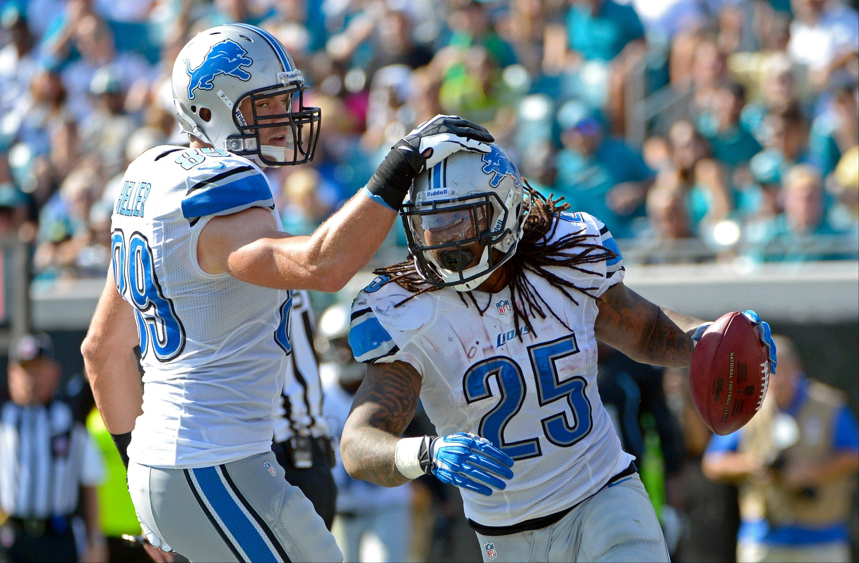 Detroit Lions running back Mikel Leshoure (25) gets a pat on the helmet from tight end Will Heller after scoring a touchdown against the Jacksonville Jaguars during the first half Sunday in Jacksonville, Fla.