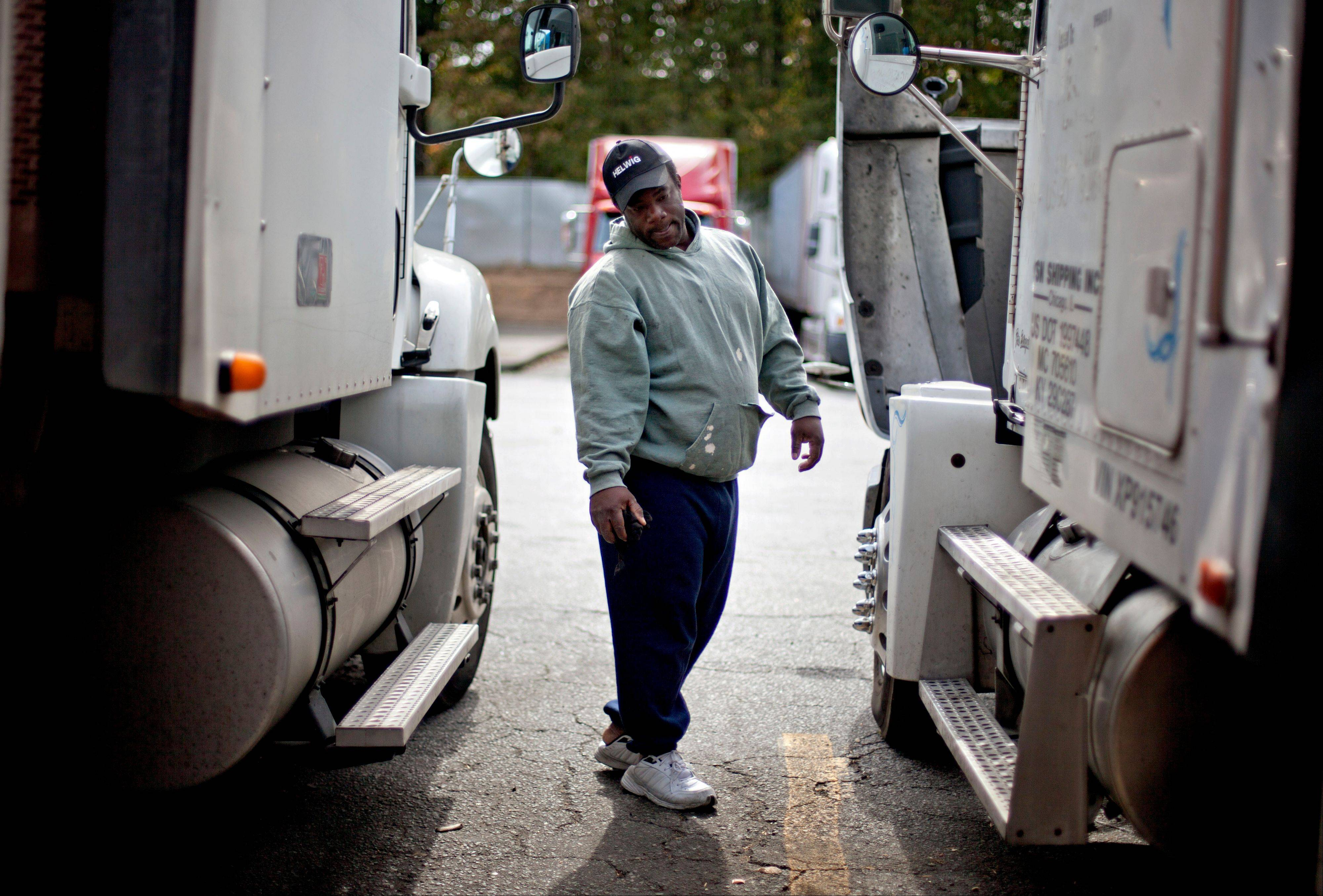 Truck driver Earliest Madir inspects his truck while waiting for a load at a truck stop Tuesday, Oct. 30, 2012, in Atlanta. Even amid a struggling economy with high unemployment, trucking companies had a tough time hiring young drivers willing to hit the road for long hauls. Now the U.S. is speeding toward a critical shortage of truck drivers in the next few years as the economy recovers and demand for goods increases, an expert in the inner-workings of supply chains said in a report Tuesday.