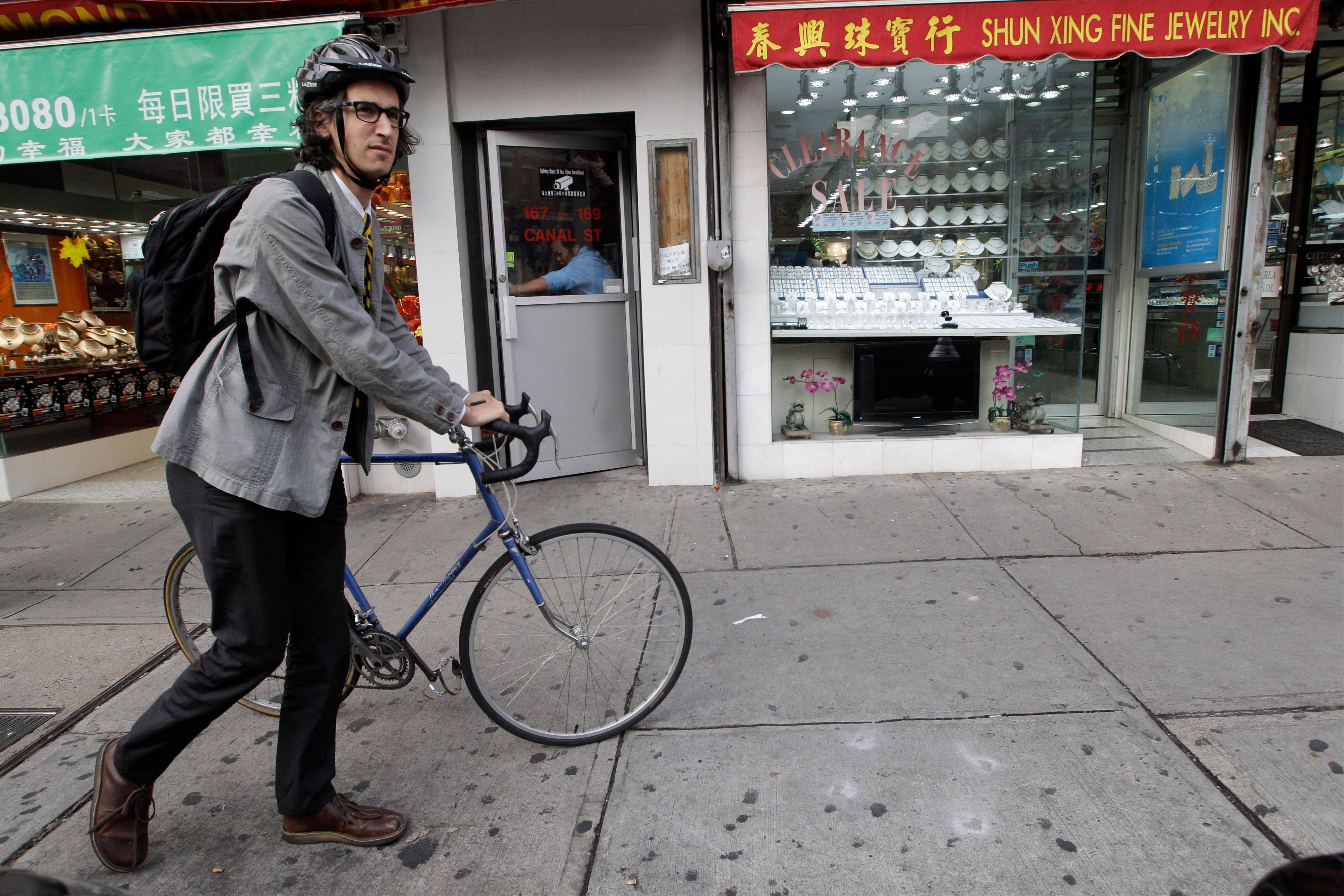 Dan Rollman, co-founder of a movement called the Sabbath Manifesto, walks his bicycle on Canal Street in New York. The Manifesto is a call to unplug one day a week to find solitude or to simply take a day of rest with family and friends.