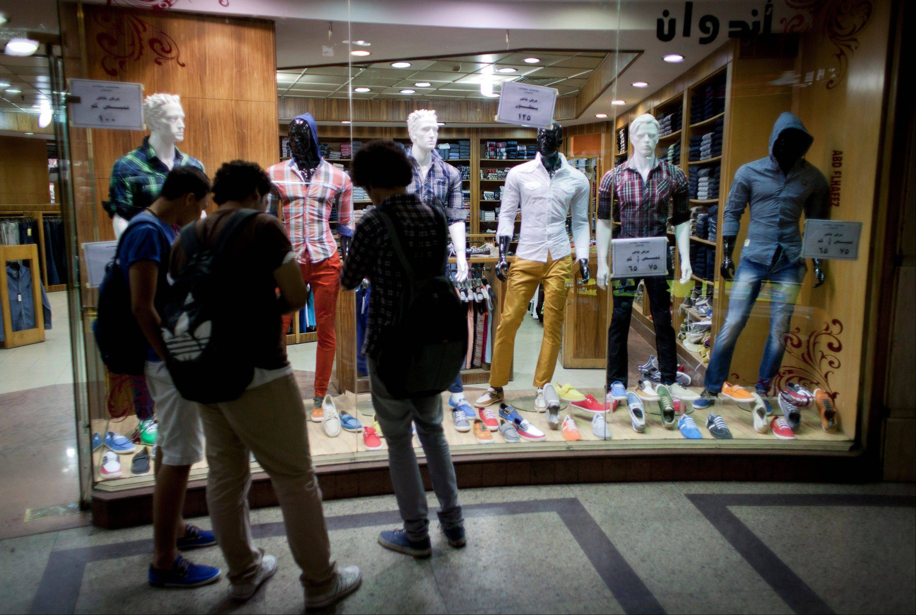 Egyptian men shop inside a commercial mall in Cairo Wednesday. Egypt's capital prides itself on being city that never sleeps, with crowds filling cafes and shops open into the small hours. So the government is facing a backlash from businesses and the public as it vows to impose new nationwide rules closing stores and restaurants early. Officials say the crisis-ridden nation has to conserve electricity, but they also seem intent on taming a population they see as too unruly.