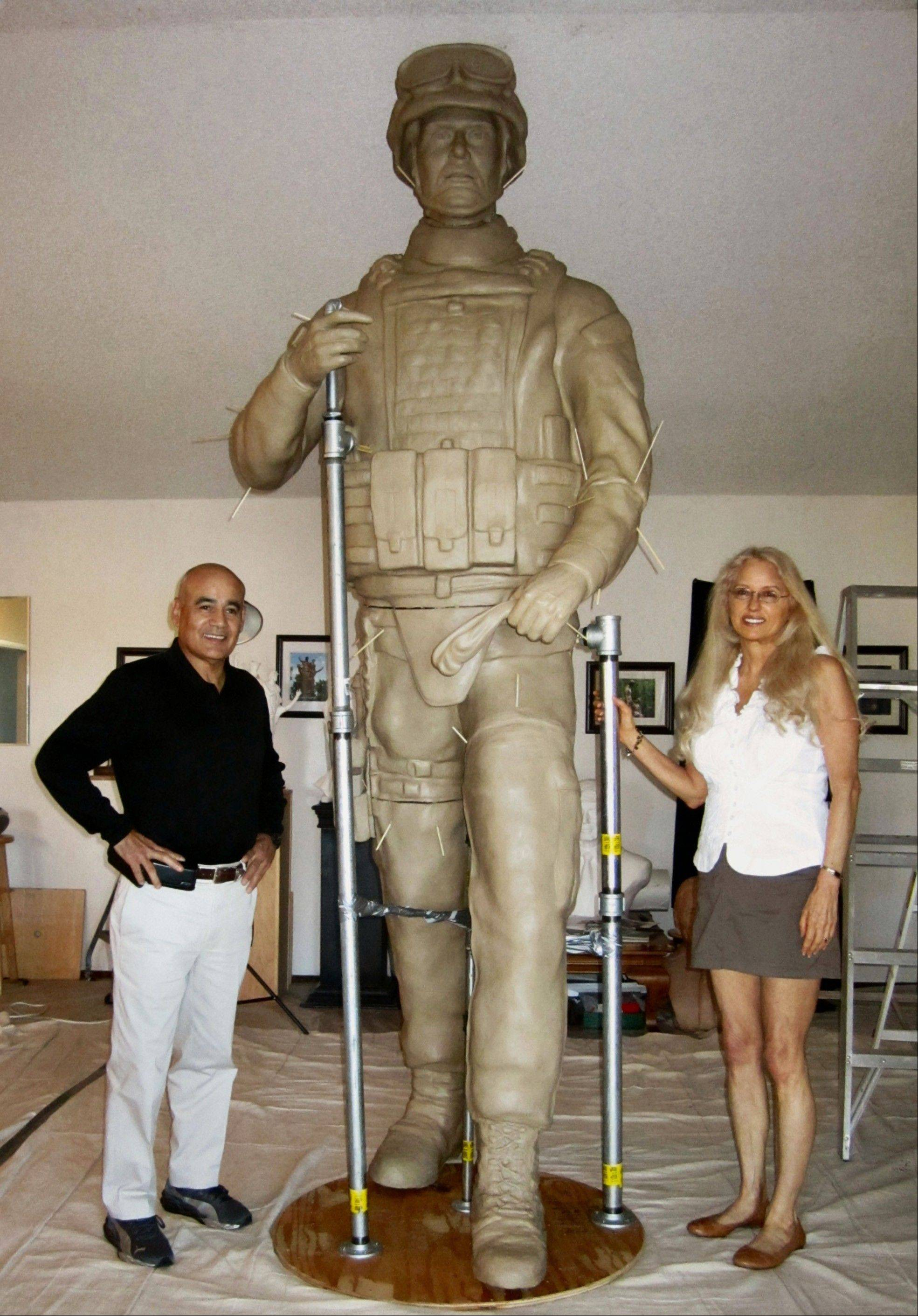In this Aug. 2, 2012, publicity photo provided by Natural Balance, war handler veteran, author and designer, John Burnam, left, and veteran portrait sculptor, Paula Slater, stand with the silicon bronze 9.5-feet tall military dog handler that is part of the U.S. Working Dogs Teams National Monument shown in the Sculptor's Studio in Hidden Valley Lake in California.