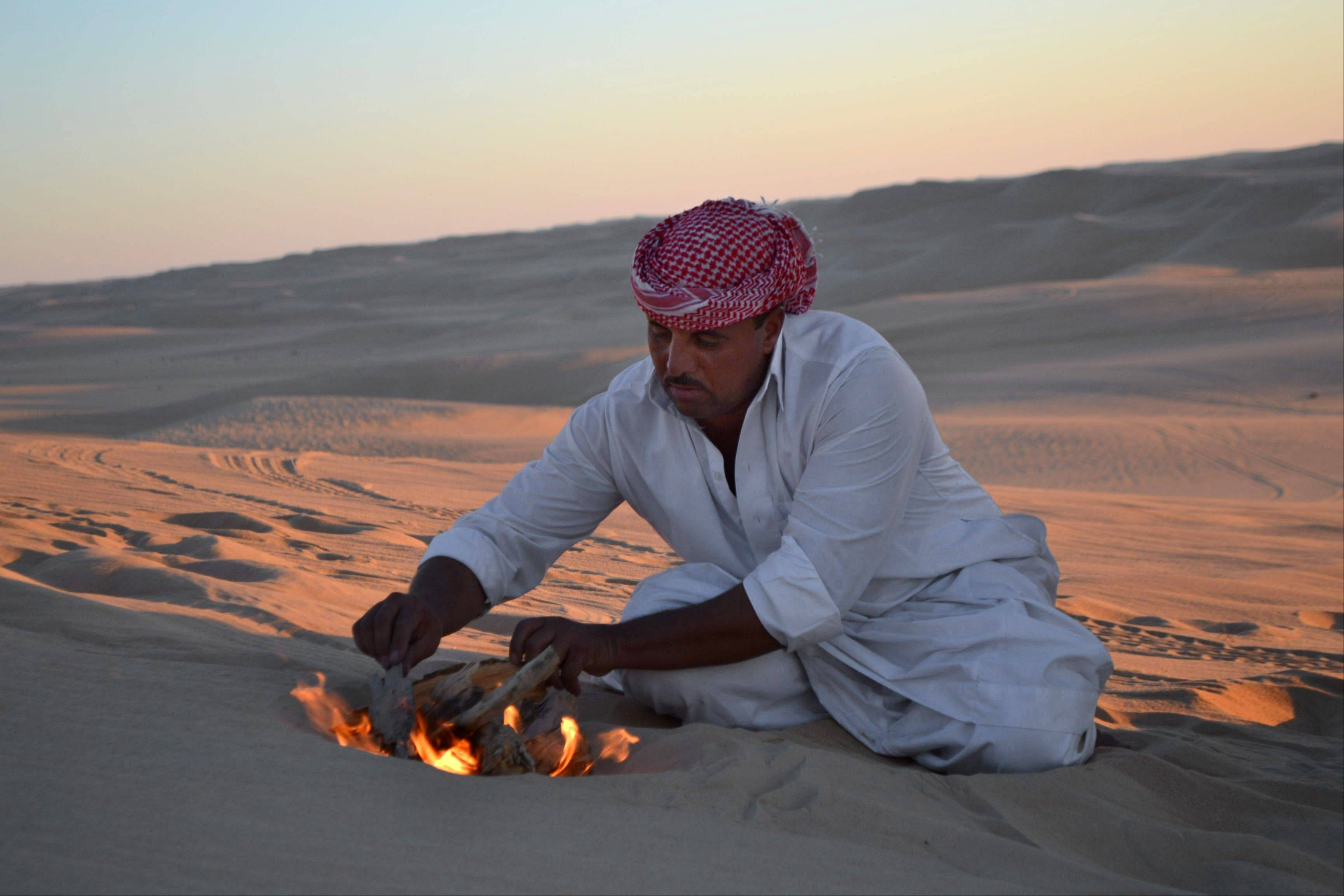 Desert safari driver Ahmed Bakrin builds a small bonfire to make mint tea before sunset during a trek through the Great Sand Sea outside the Egyptian oasis of Siwa.
