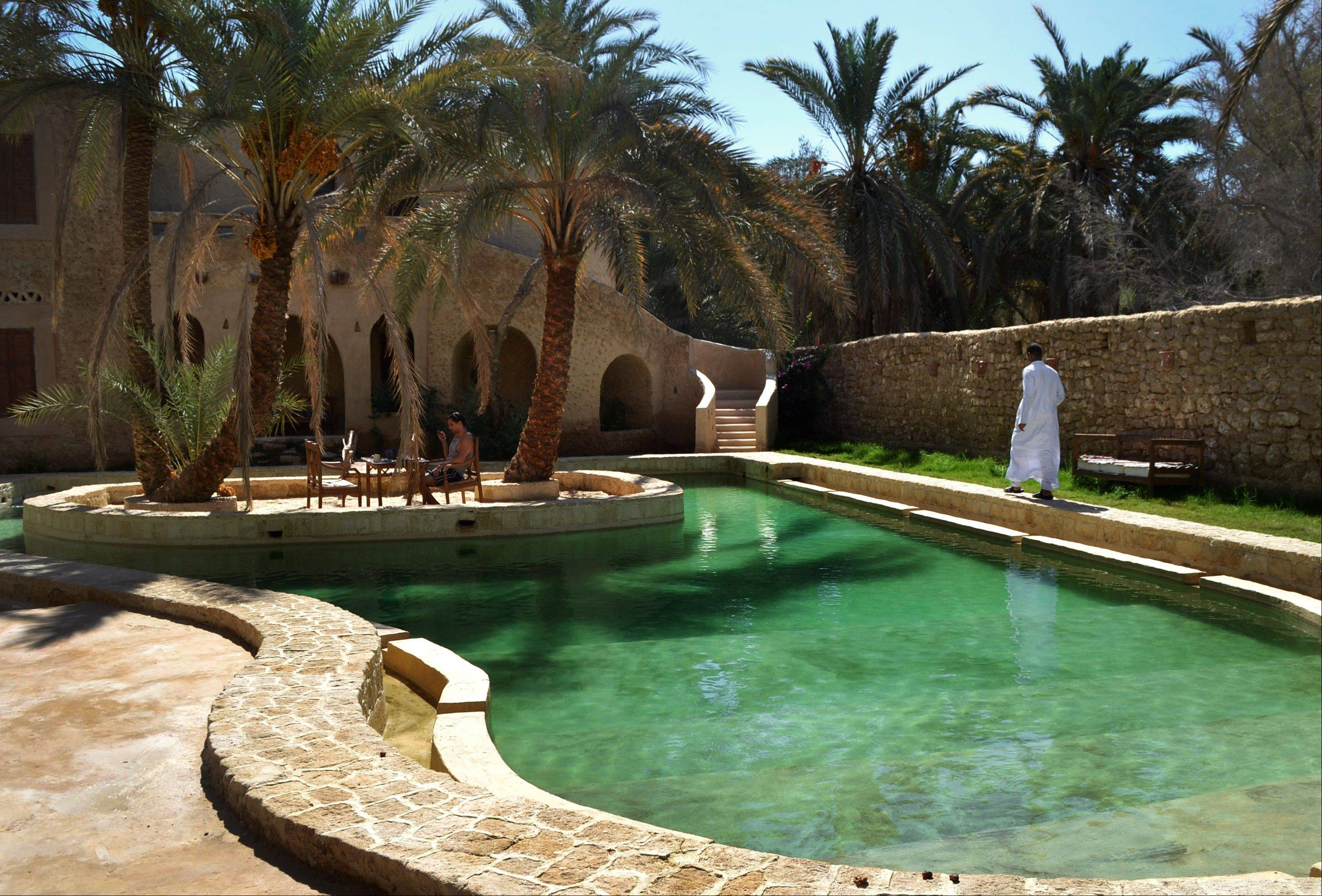 A freshwater pool at the Ghaliet Ecolodge and Spa in the Egyptian oasis of Siwa. The palm tree-lined area is known for its quiet charm, ancient ruins, natural springs, a vast salt lake and rolling sand dunes.