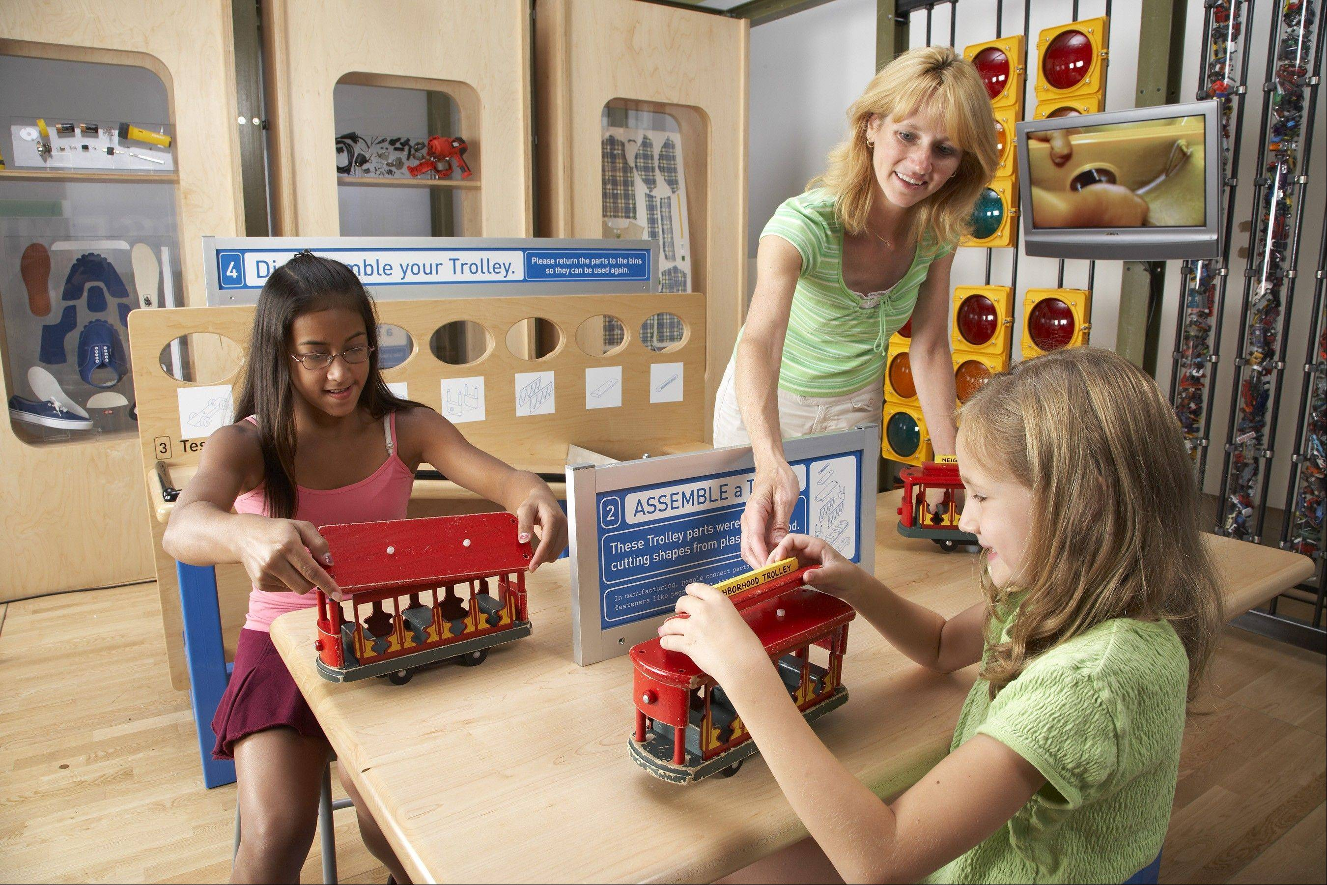 Two students see how manufacturing works and parts are joined together to create a new shape in the new exhibit How People Make Things at the DuPage Children's Museum.