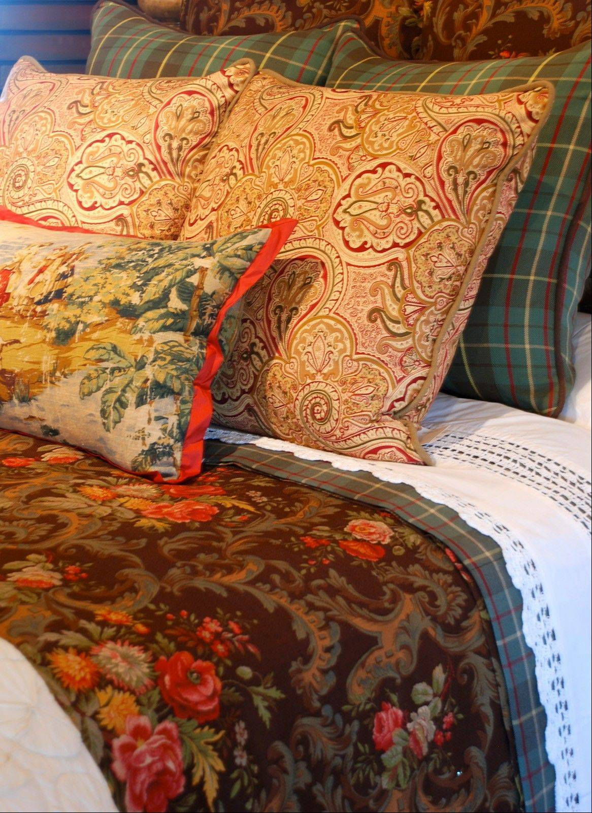 This richly dressed bed is exploding with wonderful patterns. With a mix of tartan plaid, paisley, toile and floral fabric, it looks divine.