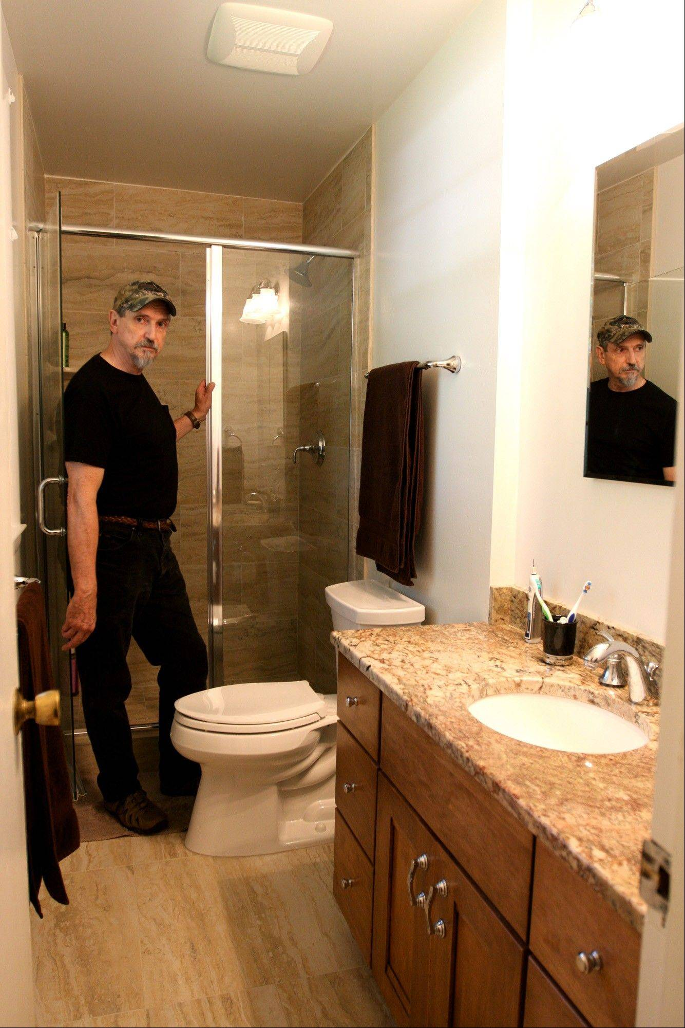 Richard Miller, pictured here, and his wife Hannah Laufe spent about $20,000 to renovate their previously pink bathroom.