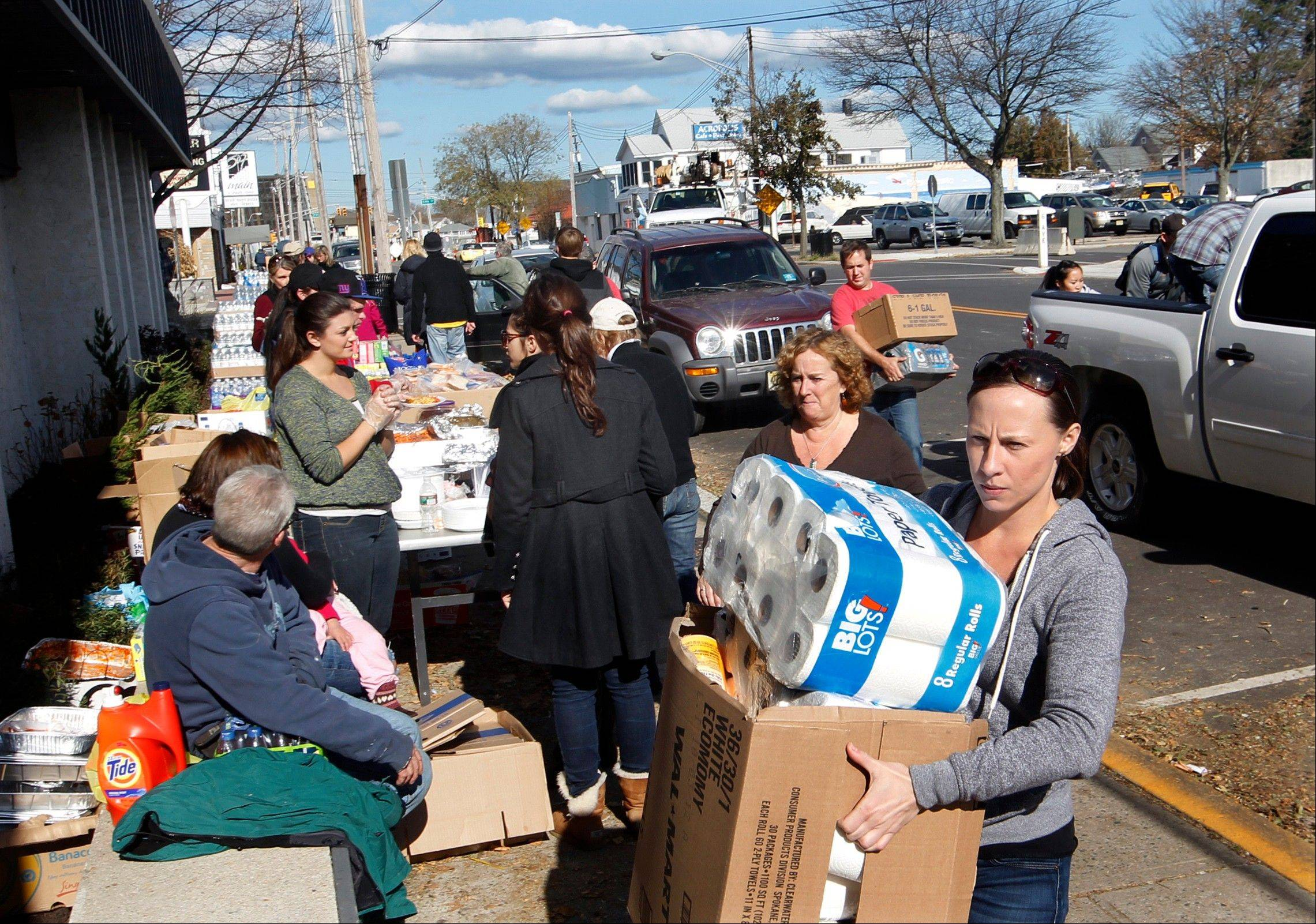 Volunteers carry donated goods into the Belmar recreation center Sunday in Belmar, N.J. After being battered by Monday's storm surge by Superstorm Sandy much of the region is still without power and many homes have been damaged.