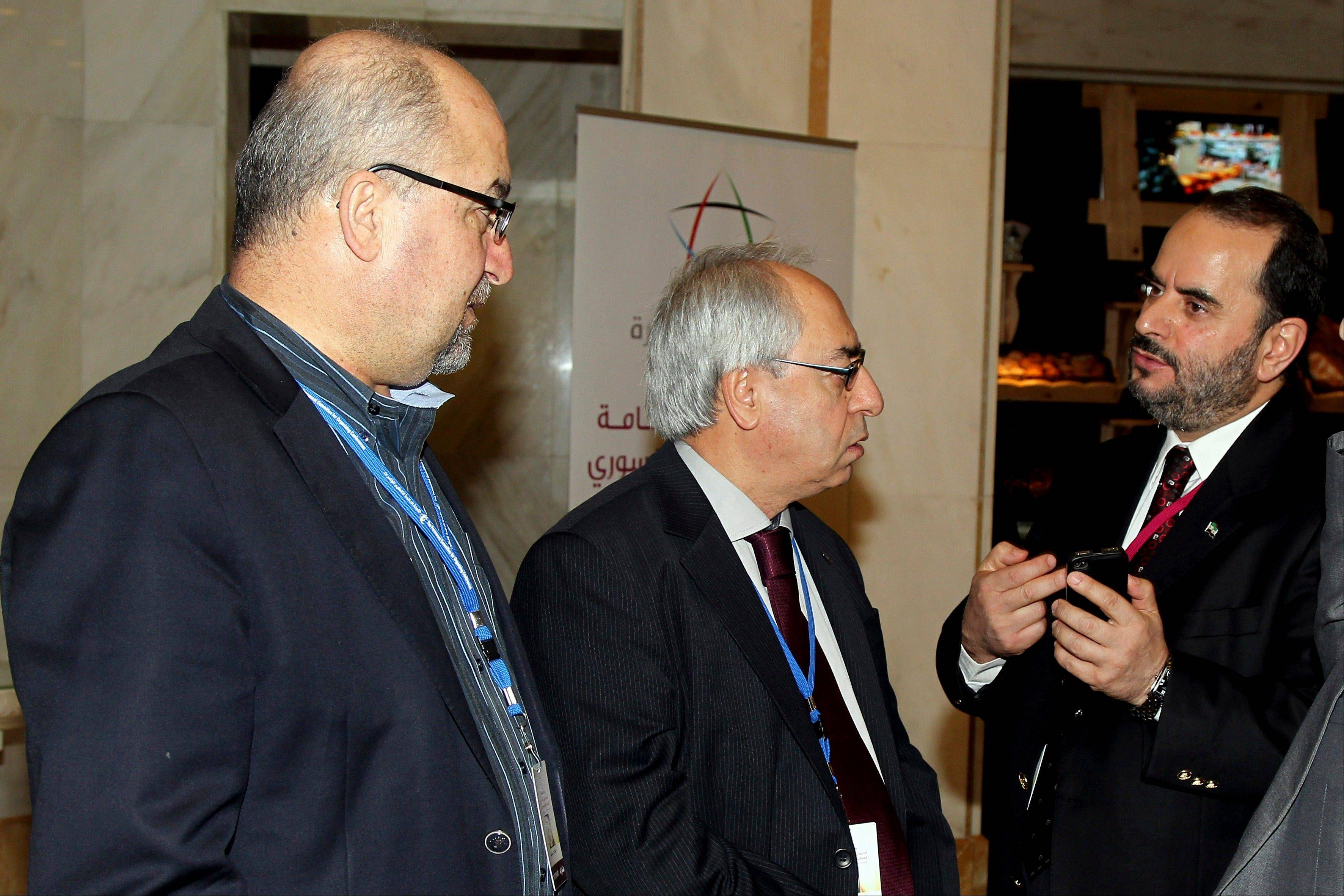 Syrian regime opponent Abdel Baset Seda, center, speaks with other participants during the meeting of the General Assem
