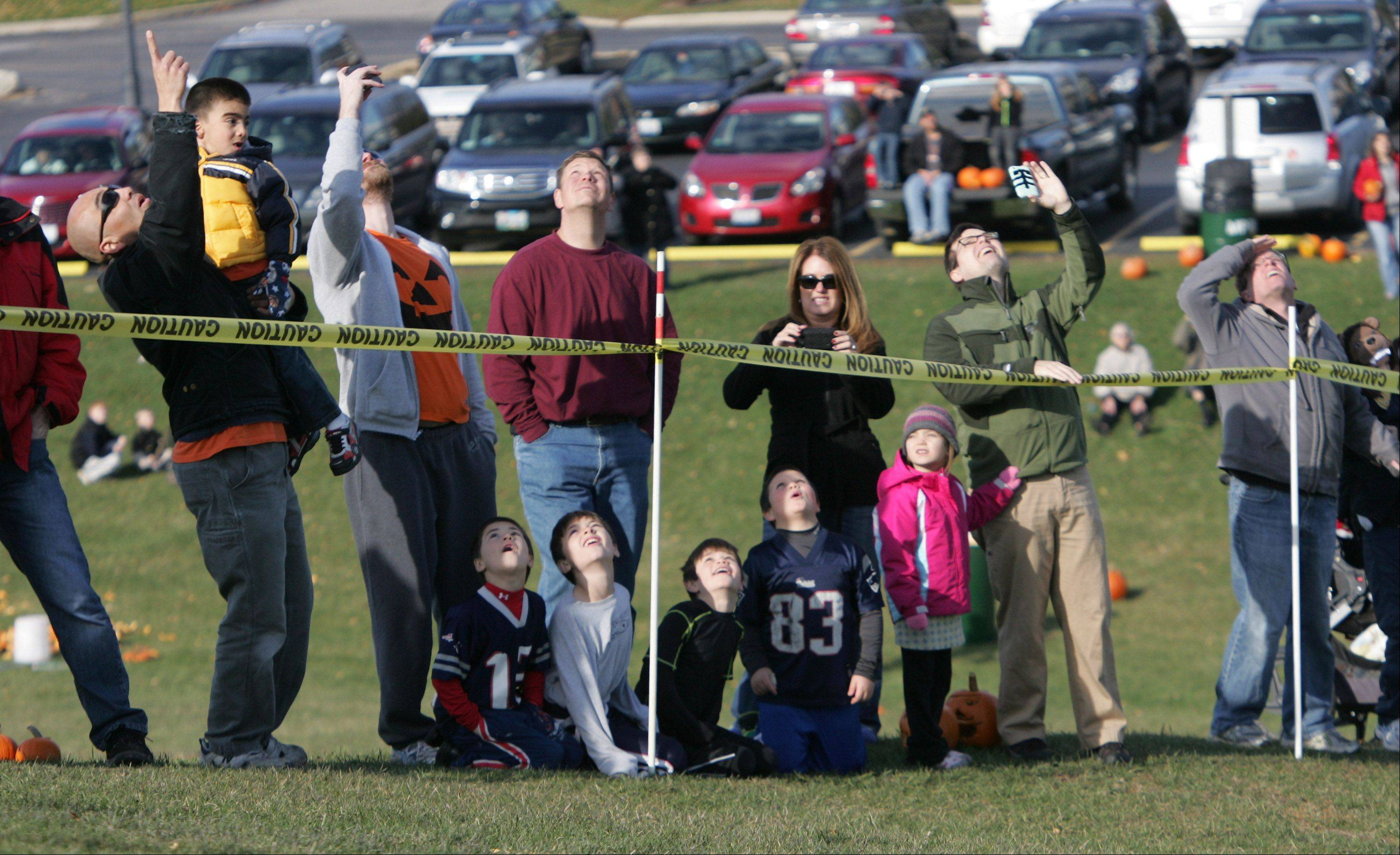 Spectators watch as a pumpkin flies through the air during the annual Pumpkin Drop hosted Sunday by the Mundelein Park & Recreation District at Keith Mione Community Park. Families and children brought their Halloween pumpkins and rolled them, smashed them and launched them using the Big Red trebuchet designed by Mundelein High School students.