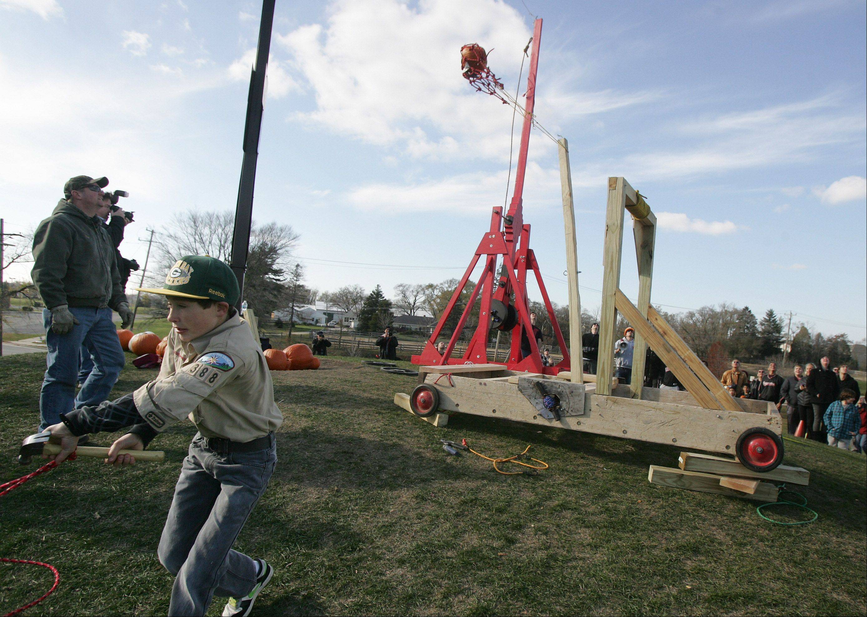 Boy Scout Jarrett Kirch, 13, left, launches a pumpkin using a trebuchet made by Mundelein Troop 388 during the annual Pumpkin Drop hosted Sunday by the Mundelein Park & Recreation District at Keith Mione Community Park. Families and children brought their Halloween pumpkins and rolled them, smashed them and launched them using the Big Red trebuchet designed by Mundelein High School students.
