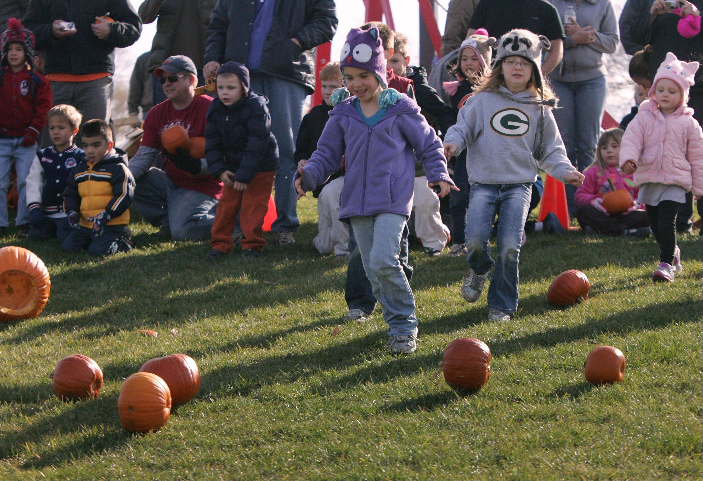 Caitlin Pron, 6, of Lake Villa, in purple, and Emma Carter, 6, of Grayslake, right, rolled their pumpkins down the sledding hill during the annual Pumpkin Drop hosted Sunday by the Mundelein Park & Recreation District at Keith Mione Community Park. Families and children brought their Halloween pumpkins and rolled them, smashed them and launched them using the Big Red trebuchet designed by Mundelein High School students.