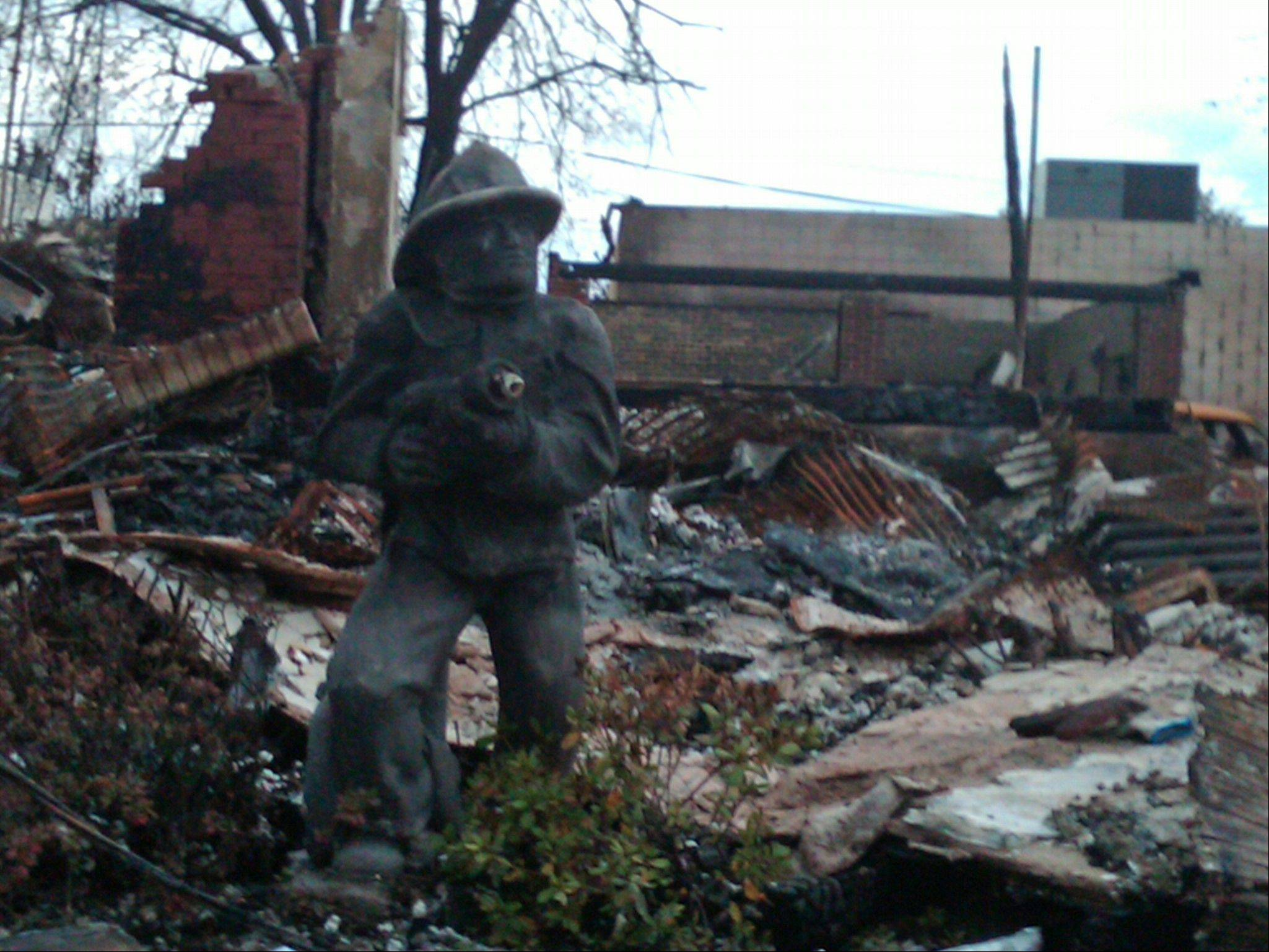 The charred remains of a firefighter statuette stands guard in front of a Belle Harbor house that burned down during Superstorm Sandy. The fire spread to 14 houses on the same street, demolishing them and forcing frightened residents to flee the fire at the height of the storm. They used a surfboard and kayaks to ferry women, children and older people to safety.