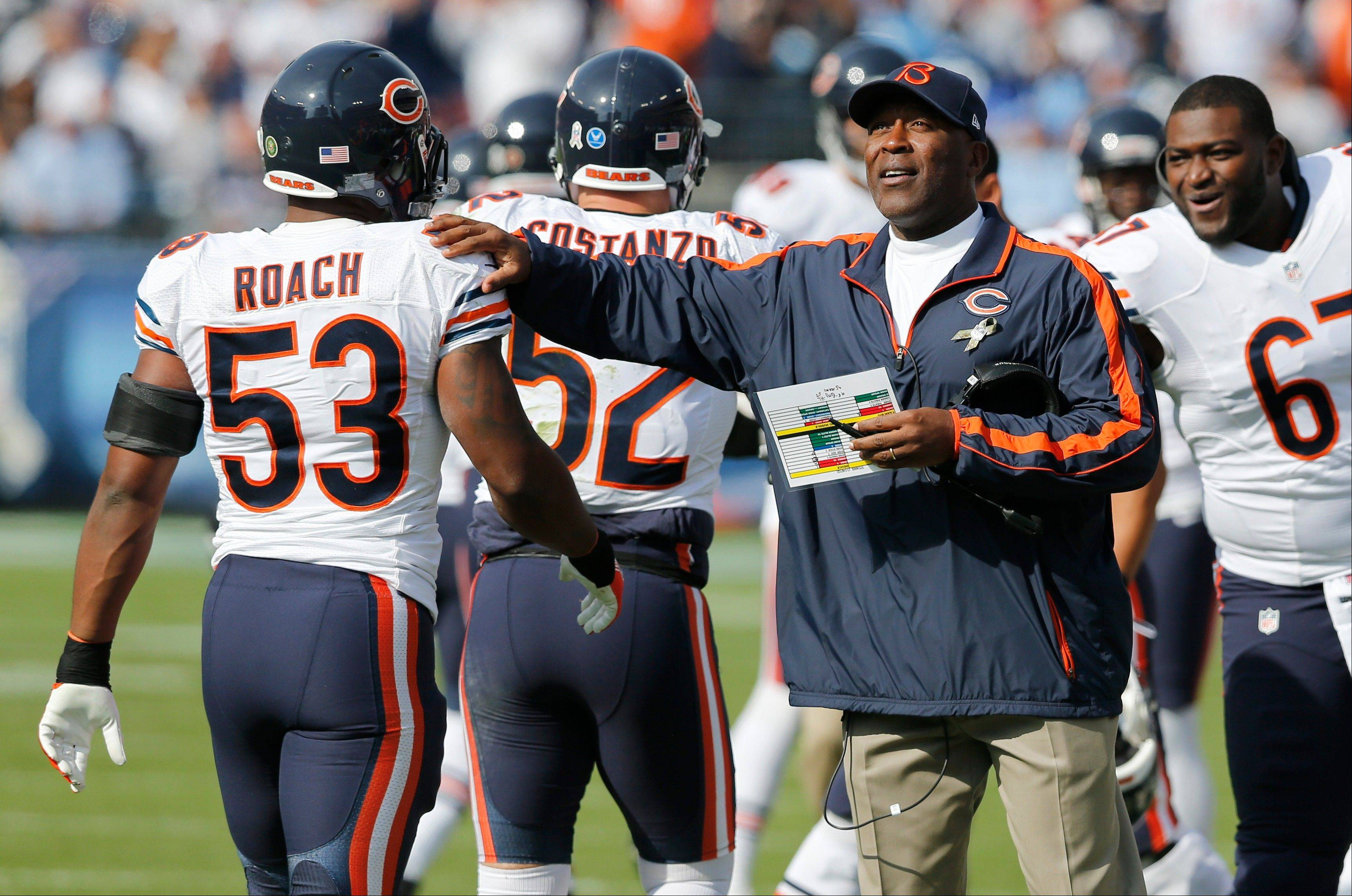 Chicago Bears head coach Lovie Smith congratulates outside linebacker Nick Roach after the Bears scored a touchdown on a blocked punt against the Tennessee Titans in the first quarter.