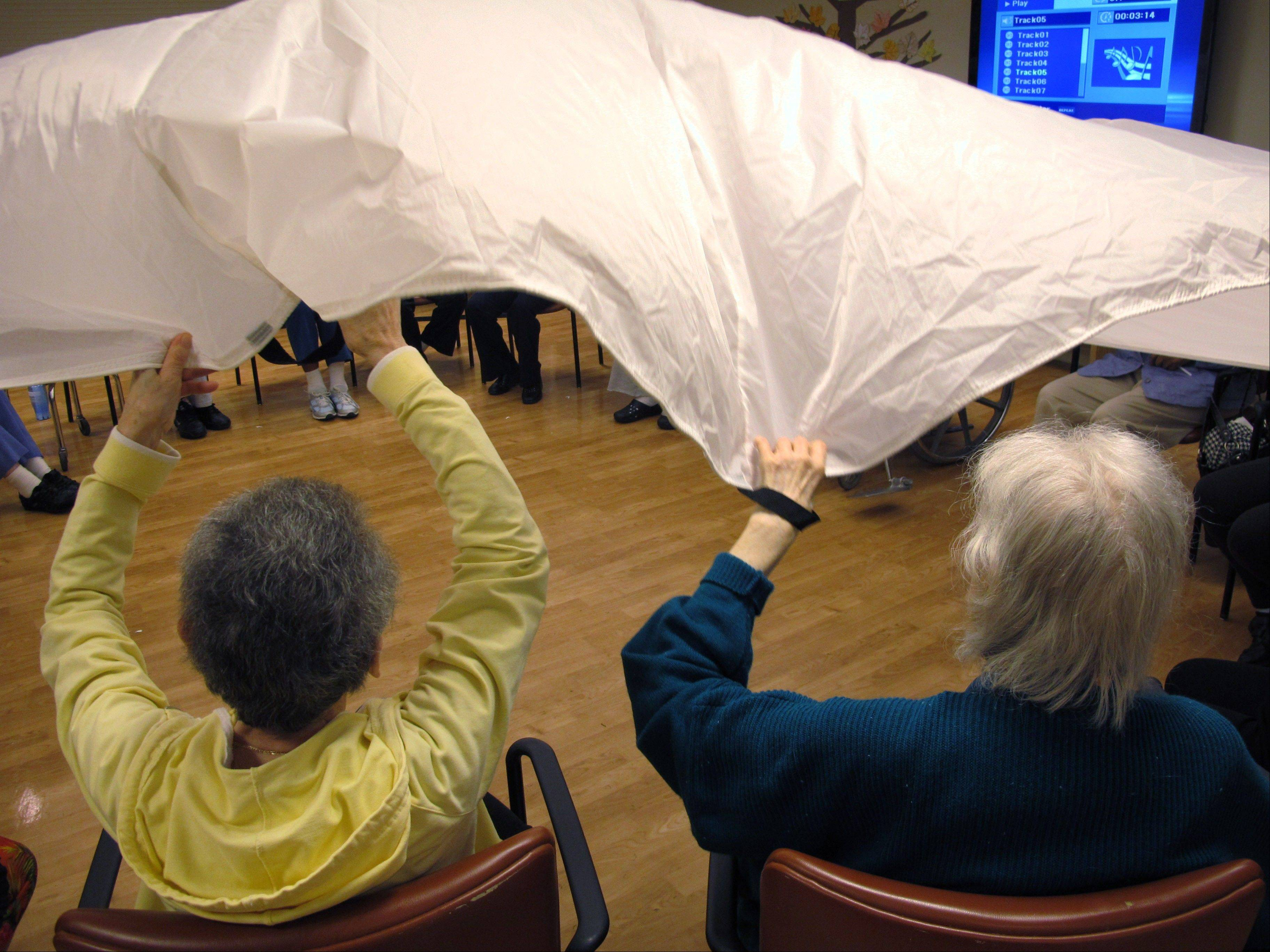"Dementia patients sitting in a circle formation do an exercise called ""the parachute"" at the Hebrew Home at Riverdale in the Bronx borough of New York. The Hebrew Home has a program that provides care and activities overnight for dementia victims with sleep problems."