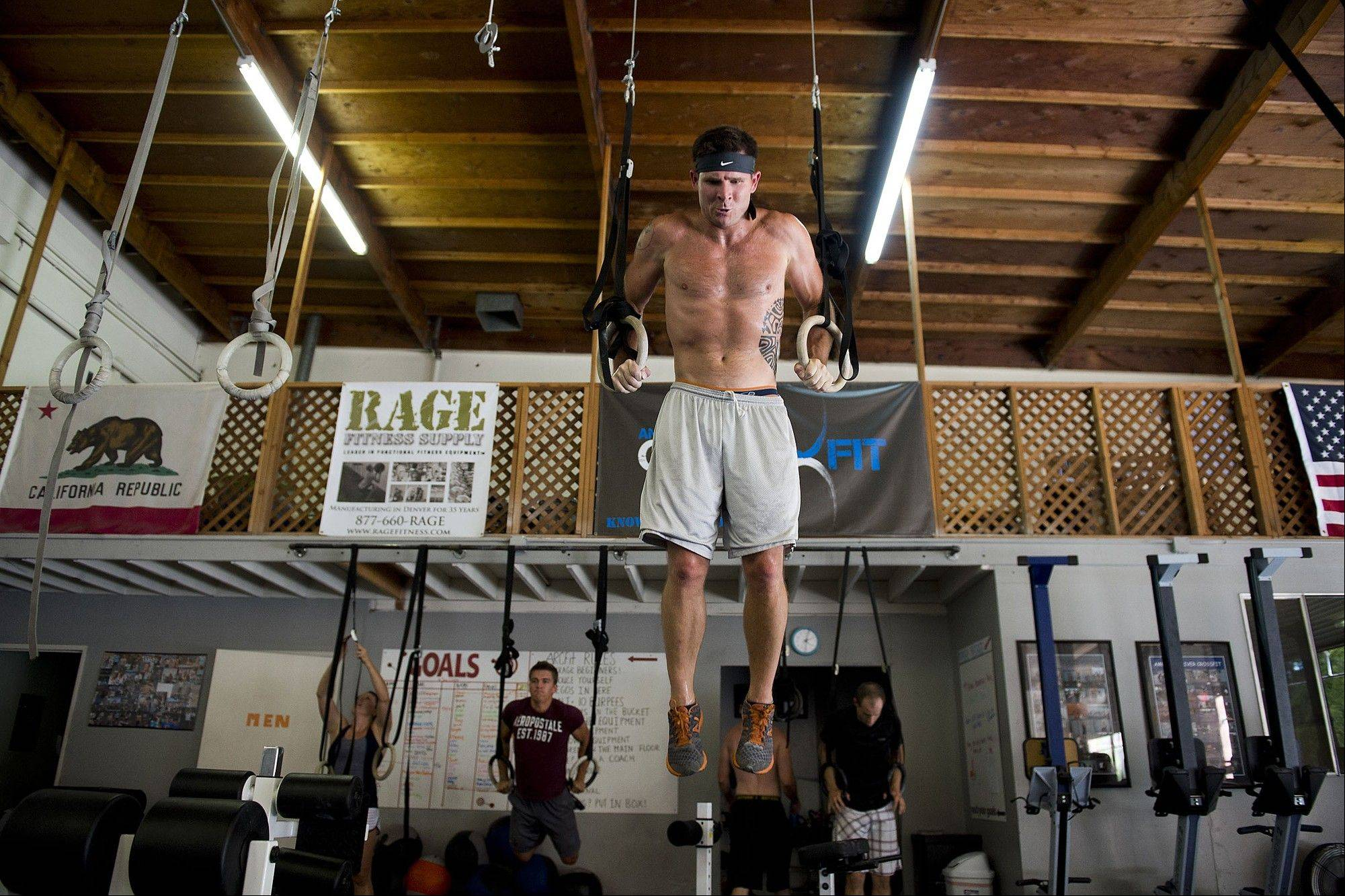 Trevor Remick exercises his upper body, performing dips on the rings at the American River CrossFit Gym in Sacramento, Calif.