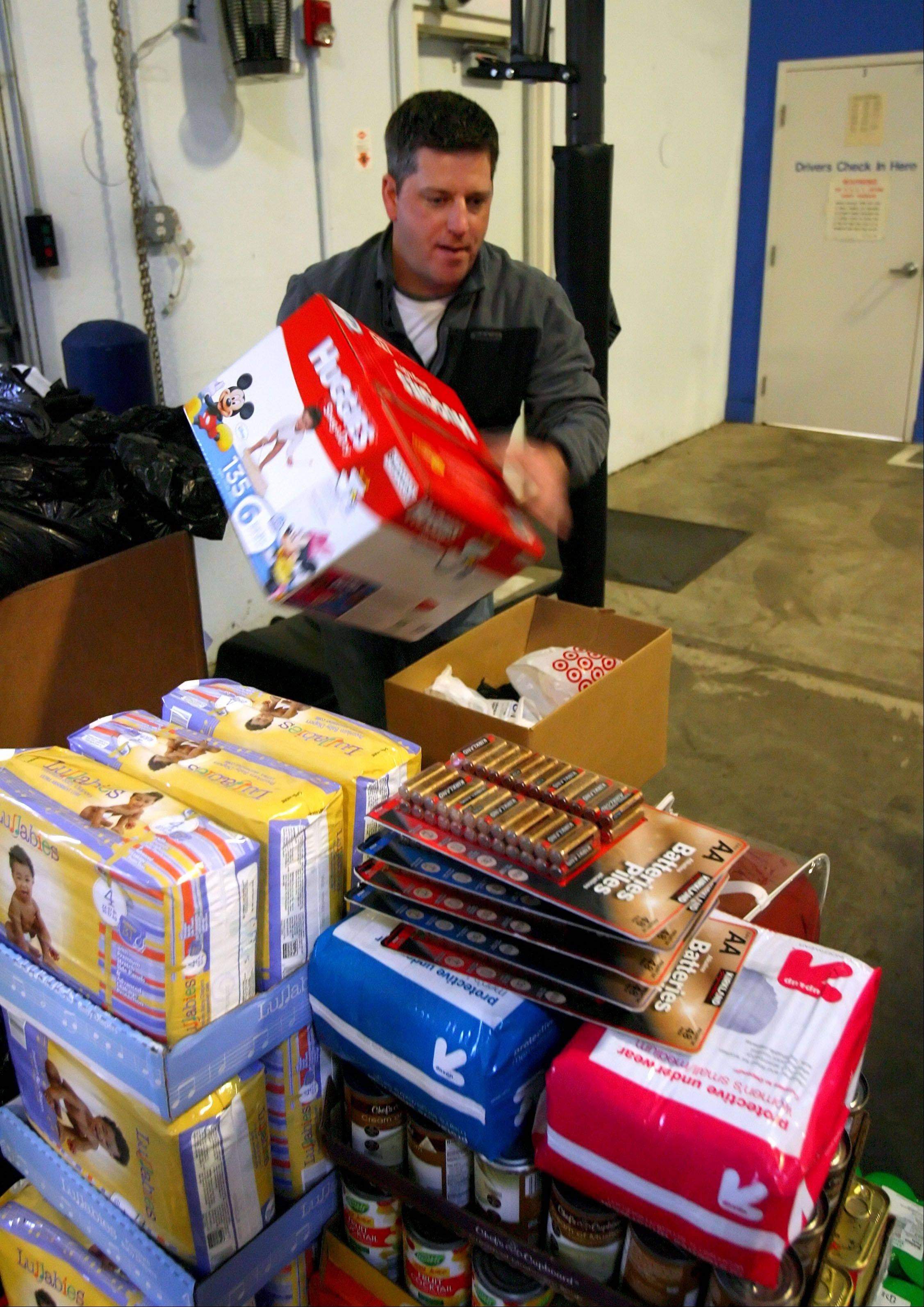 Warehouse manager Dave Rohr stacks donated items at New Age Transportation. The Lake Zurich company is collecting flashlights batteries, diapers and other non-perishable goods for the Hurricane Sandy relief effort in New Jersey. Donated items must be new and can be dropped off at the facility at 1881 Rose Road during normal business hours.