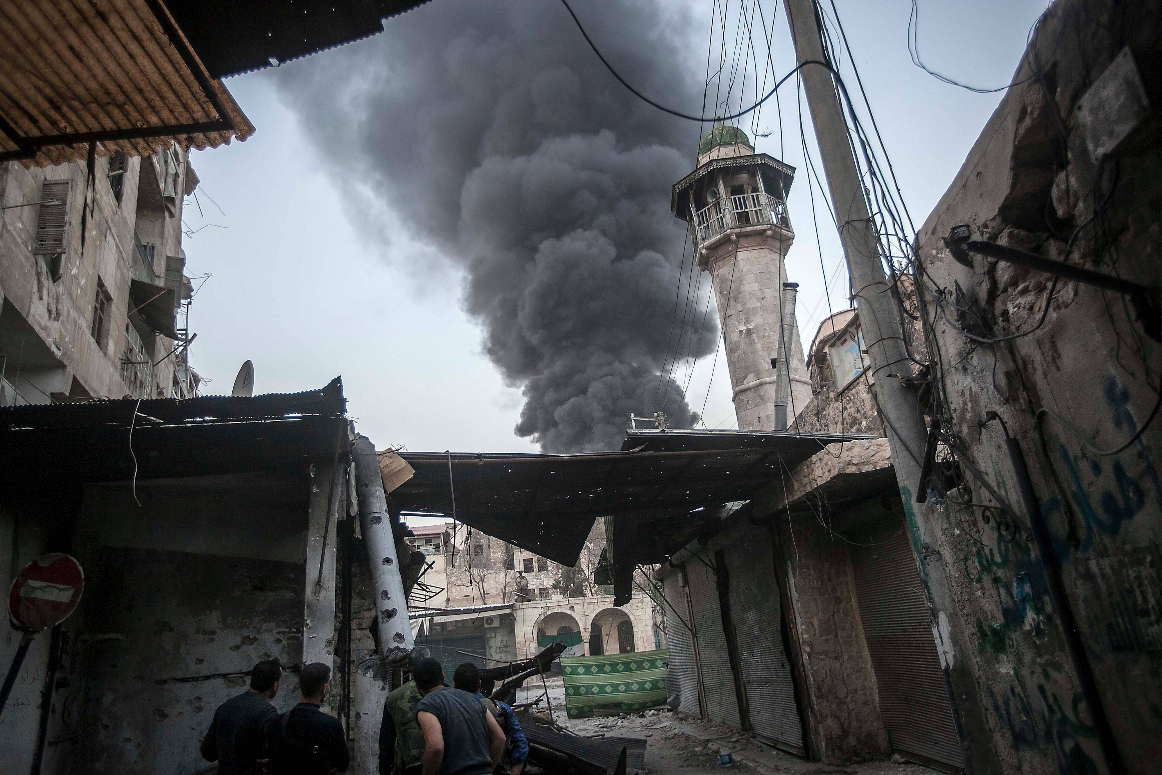 Rebel fighters watch as smoke rises Sunday after Syrian government forces fired an artillery round at a rebel position during heavy clashes in the Jedida district of Aleppo, Syria.