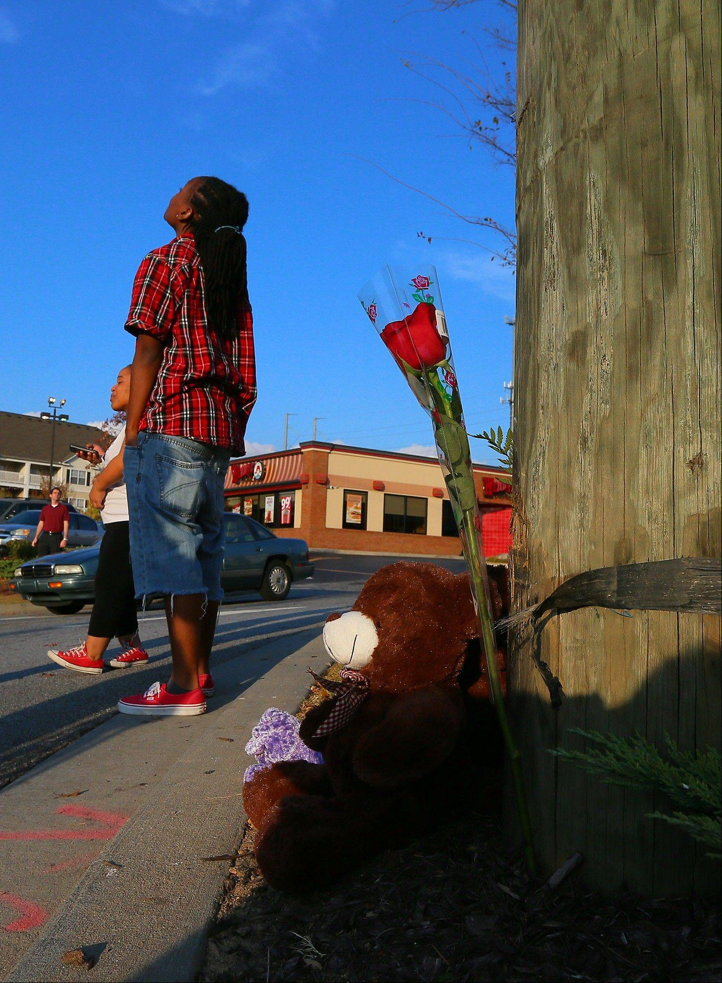 Local resident Ciara Edmonds glances up at telephone wires and lines Sunday after placing a rose on a shrine of the crash site where a police helicopter crashed killing two officers in Atlanta. The crash occurred Saturday during a search for a missing child.