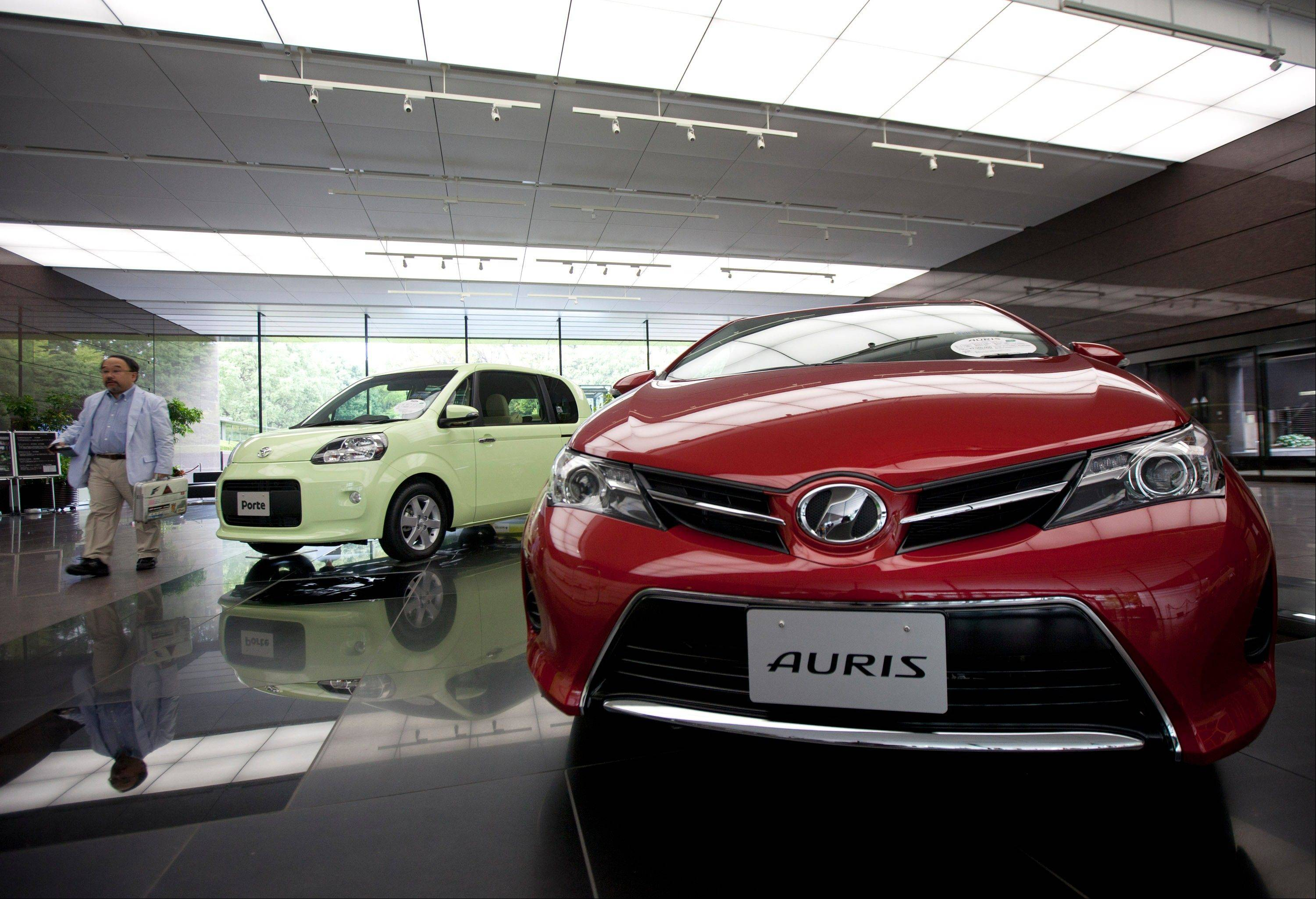 A visitor walks near a Toyota Motor Corp. Auris compact vehicle, right, displayed at the company's head offices in Tokyo, Japan, on Monday, Nov. 5, 2012.