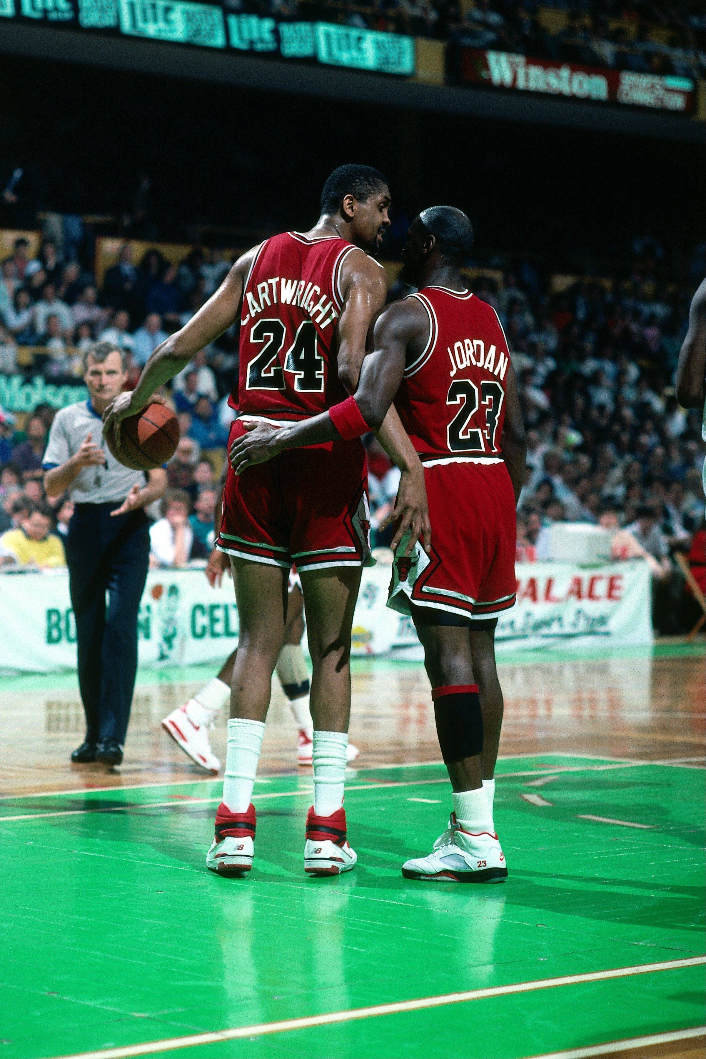 Michael Jordan (No. 23) and Bill Cartwright (No. 24) of the Chicago Bulls talk on the court against the Boston Celtics during a game played in 1990 at the Boston Garden in Boston, Mass.