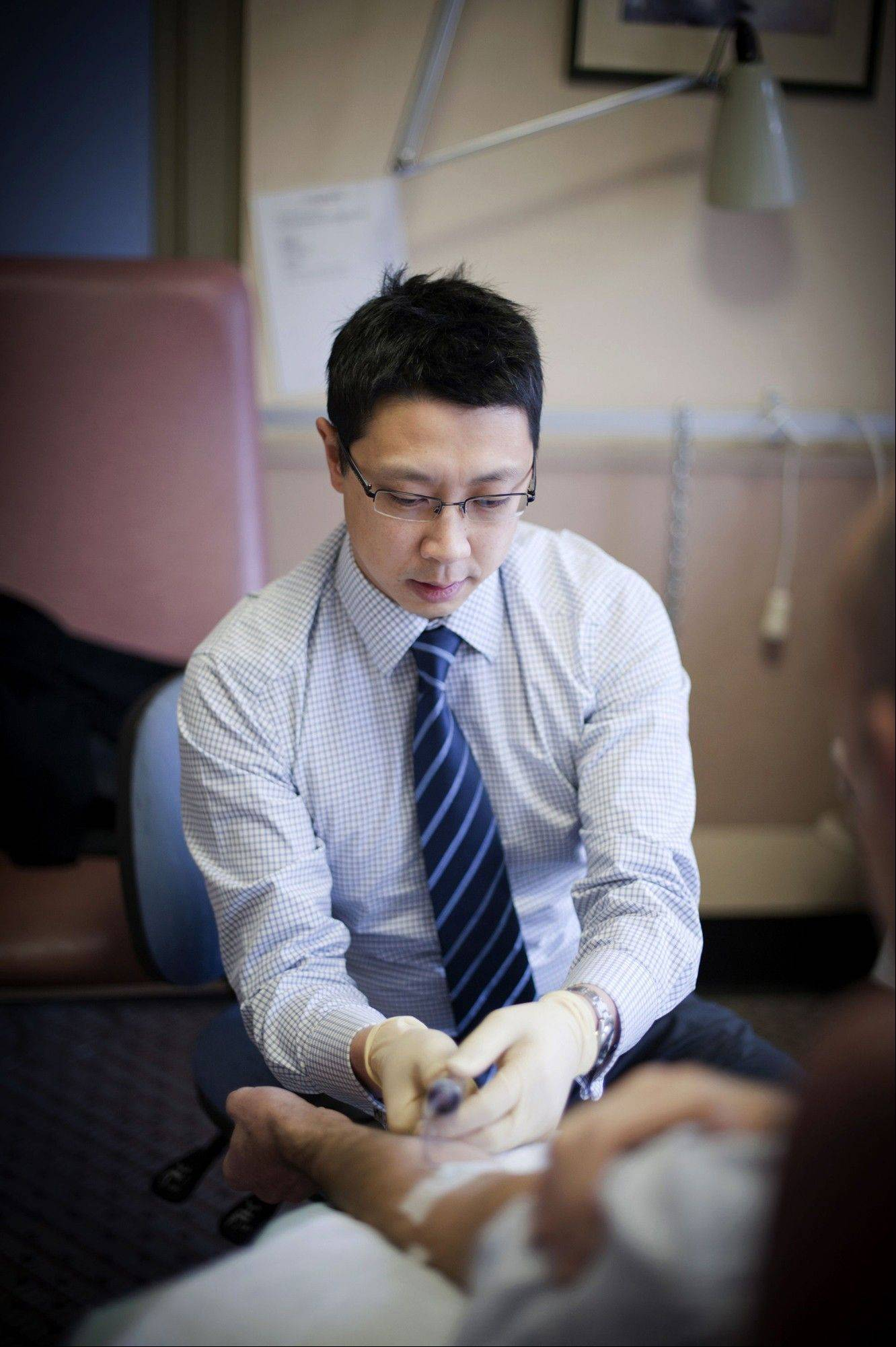 Dr. Jason Tye-Din collects blood from a patient at the Walter and Eliza Hall Institute of Medical Research in Melbourne.
