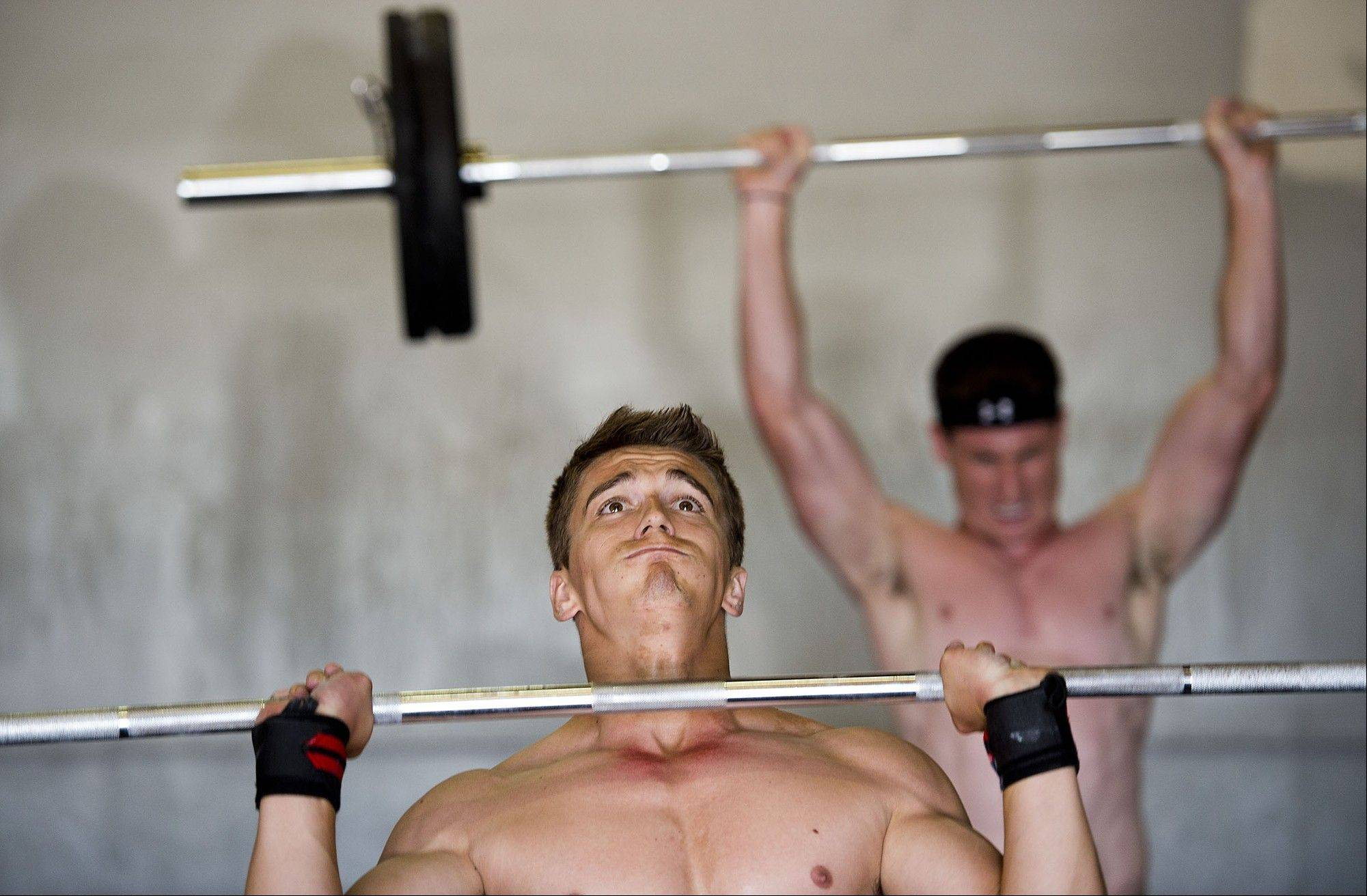 Austin Penna, left, and Kevin Beppe work out with the push press exercise at American River CrossFit Gym in Sacramento, Calif.