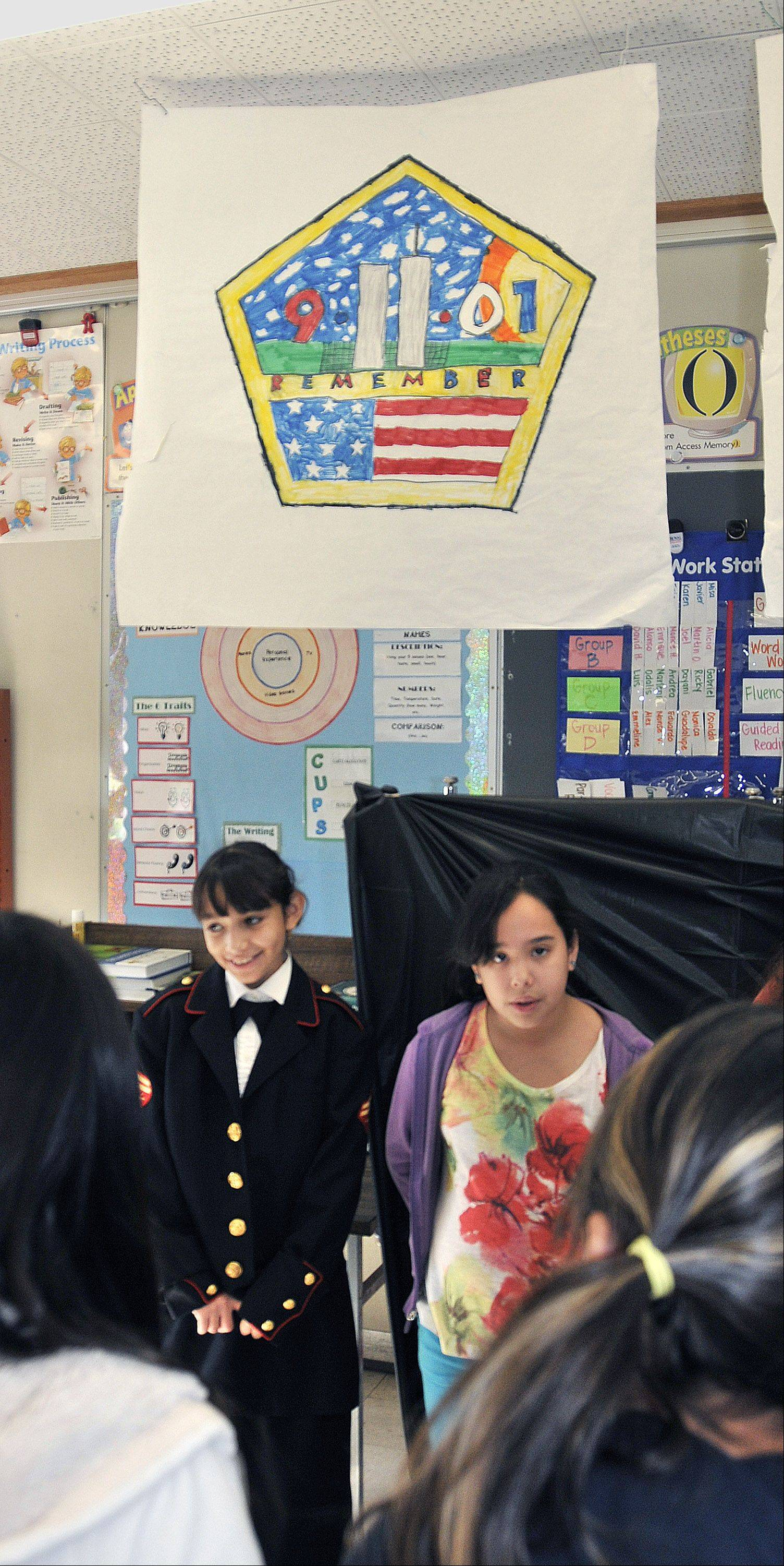 With a backdrop of a drawing remembering the 911 terrorist attacks, Cynthia Espino is a U.S. Marine and Jacquelen Alacantra portrays a New York resident. Fifth-grade students at Gary School in West Chicago presented a living history for Veterans Day.
