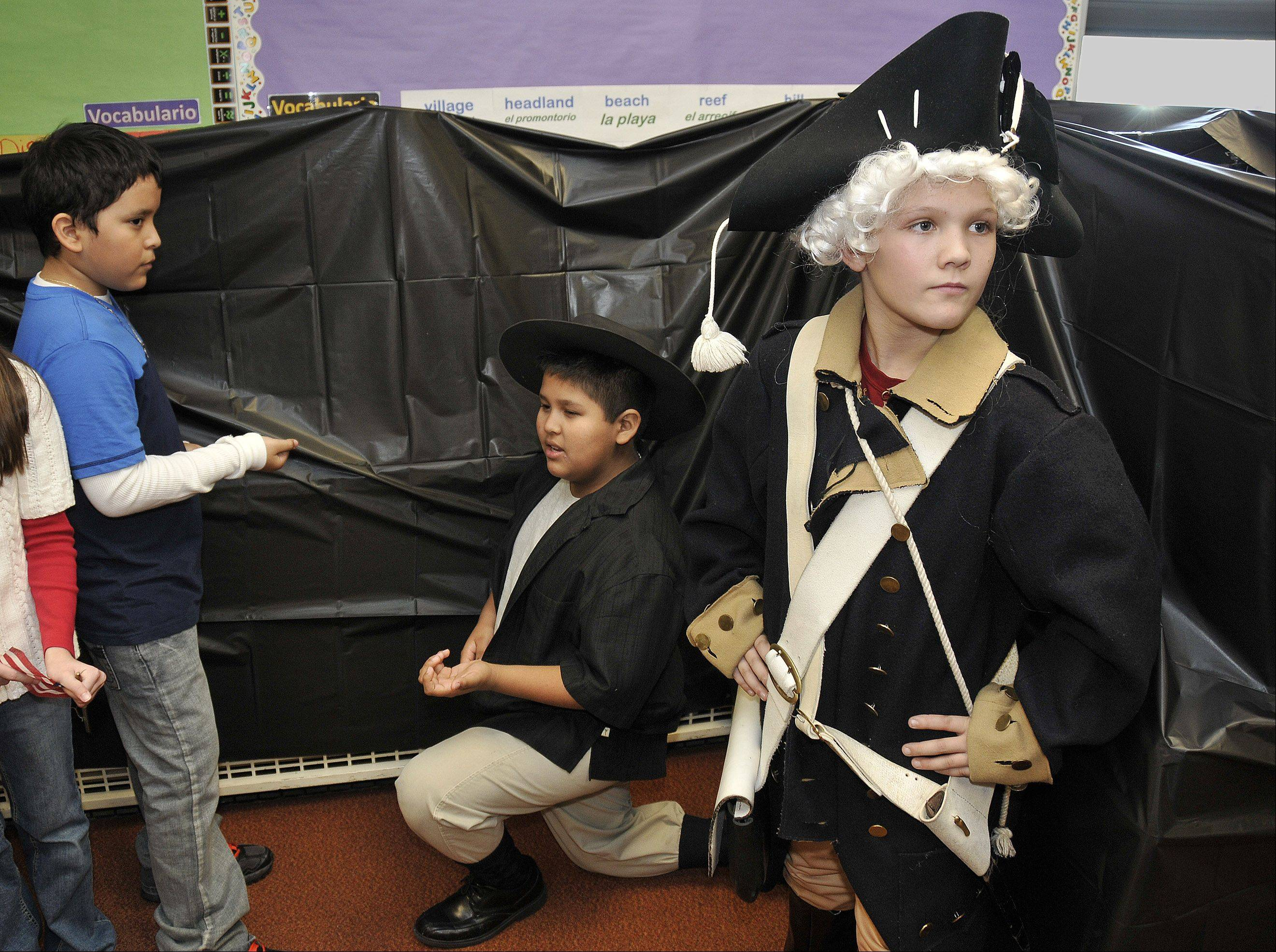 Enrique Villagran, left, posing as a British soldier, holds an imaginary gun on Continental Army soldier Eric Coss. Austin Shwatal, right, as General Washington, stoically looks away.