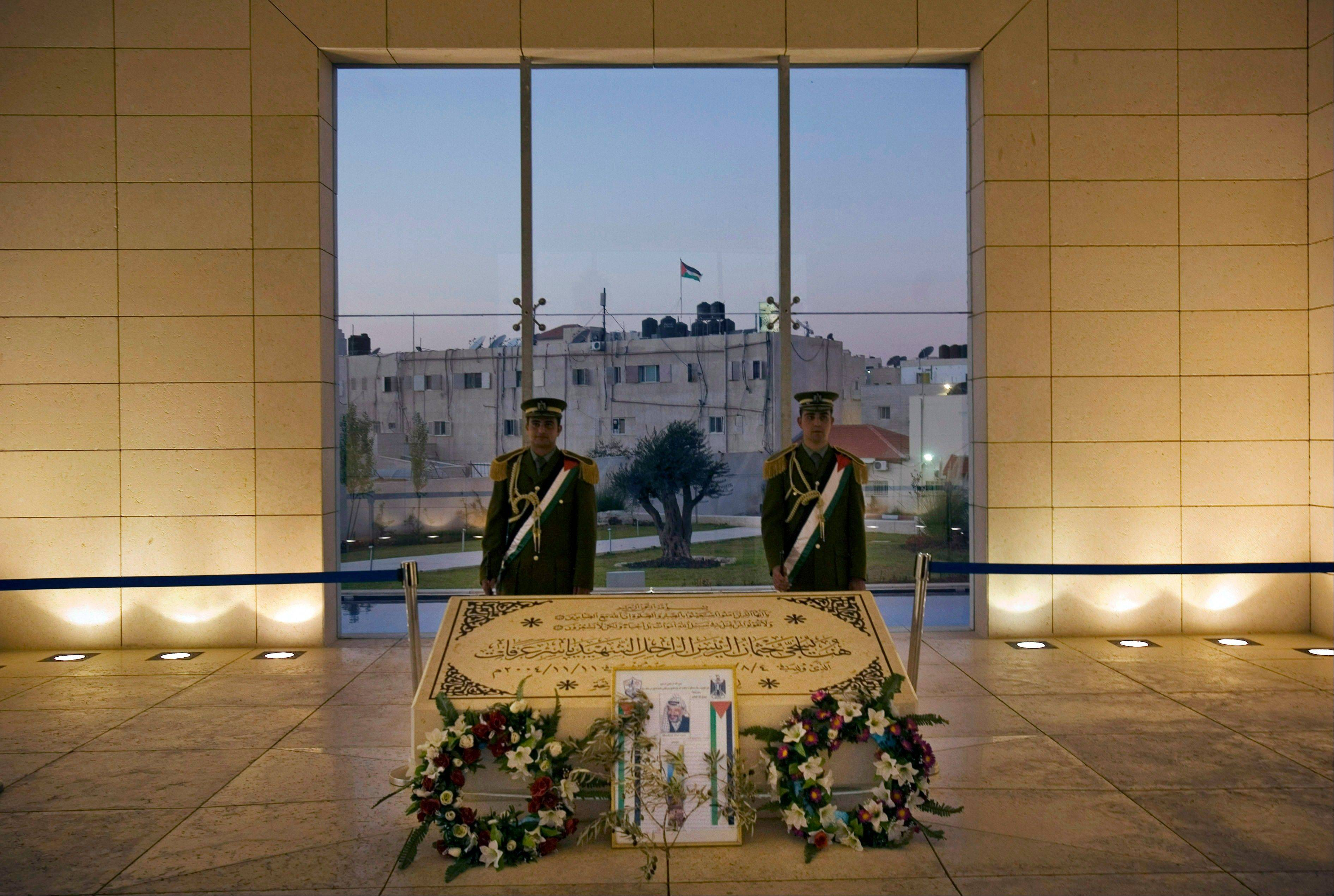 Members of the Palestinian Presidential Guard stand at the grave of the late leader Yasser Arafat in the West Bank city of Ramallah. Arafat's remains will be exhumed Nov. 26, a Western diplomat said Monday, as investigators began determining how best to dig up the grave and extract samples.