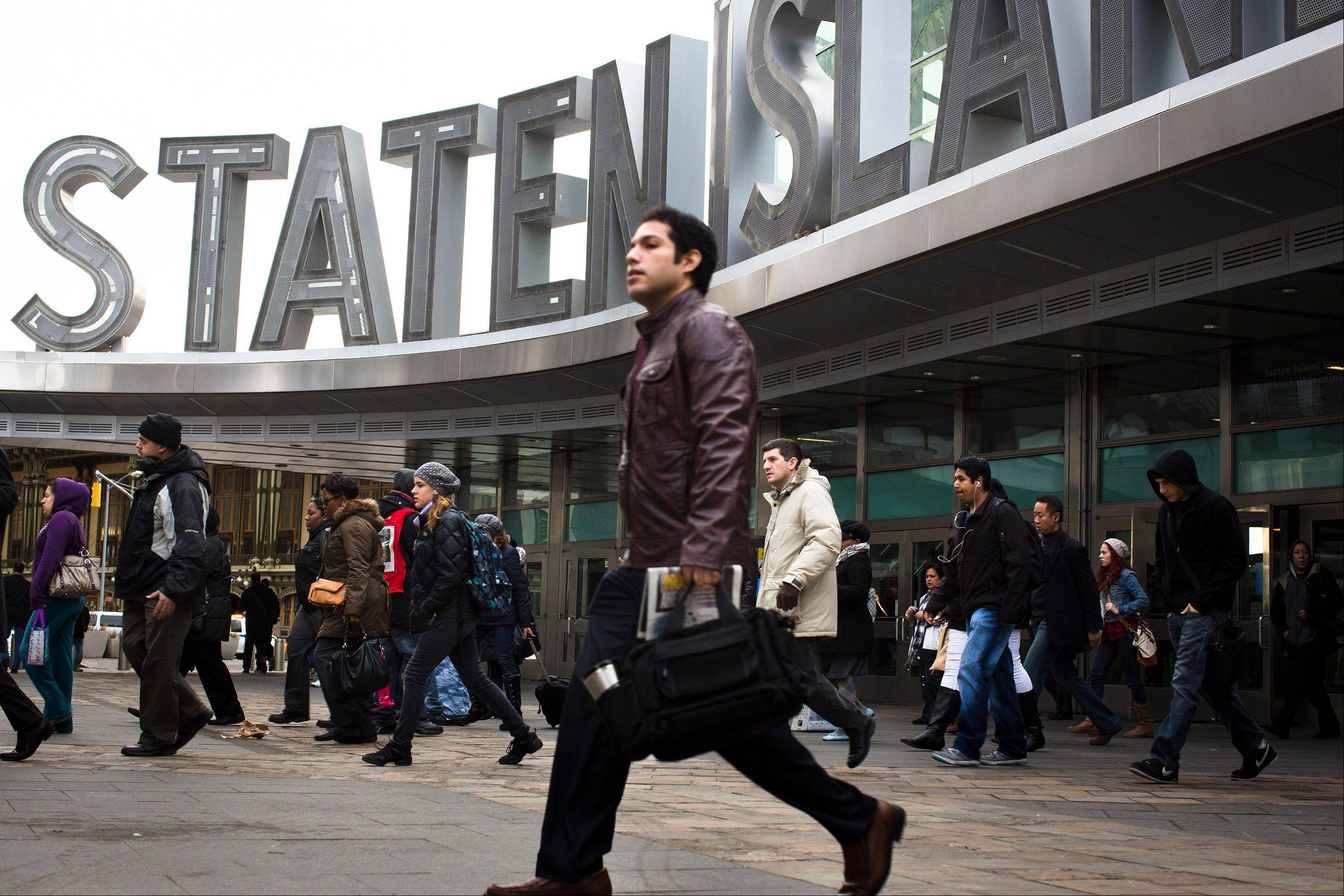 A commuter leaves the Staten Island Ferry terminal, Monday, one week after Superstorm Sandy crashed into the metropolitan area, wreaking havoc and shutting down mass transit services for days, in New York. The island of Manhattan has begun to return to normal following a week of power outages that shuttered businesses and left many residents in the dark.