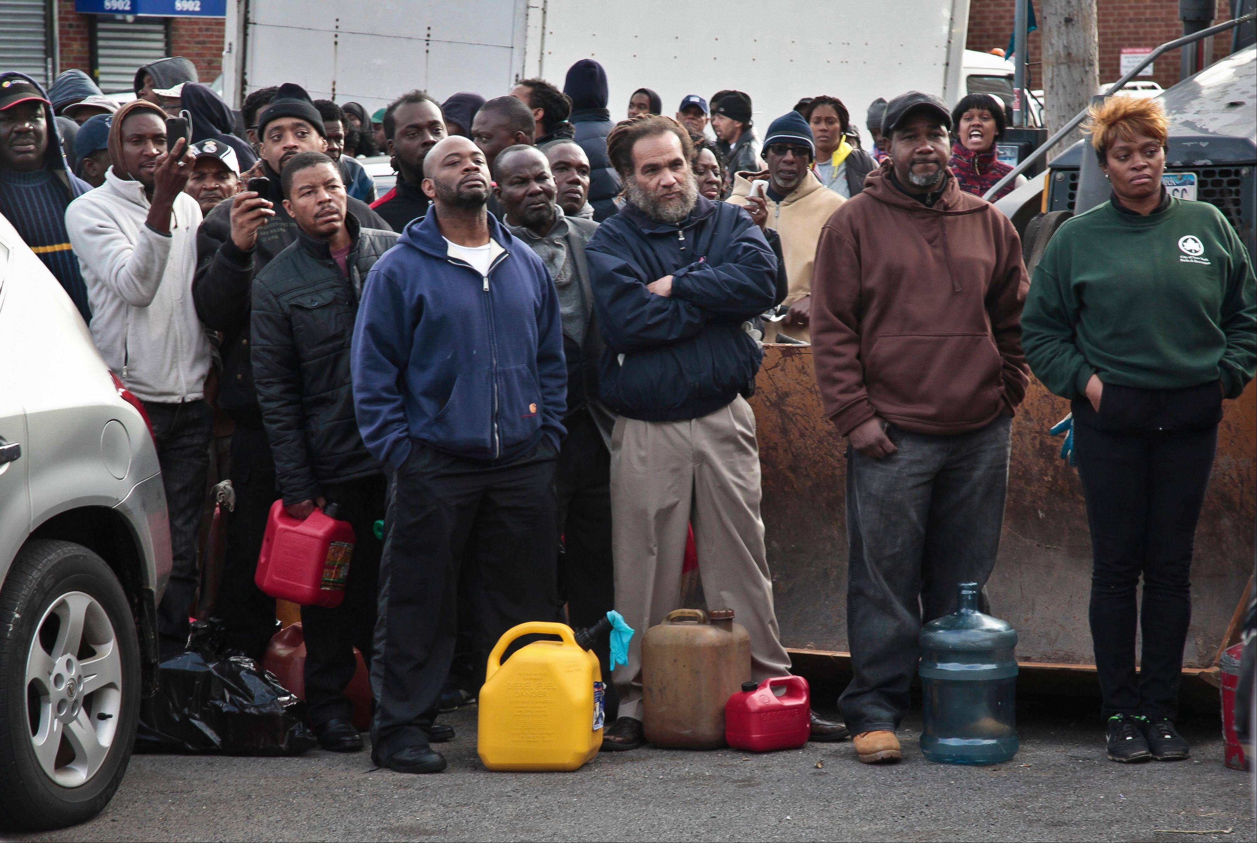 A crowd gather at a service station with portable containers, waiting for gas pumps to open, Saturday in the Brooklyn borough of New York. Mayor Michael Bloomberg said that resolving gas shortages could take days. Police presence was increased at gas lines after arrests happened at gas stations over line jumping.