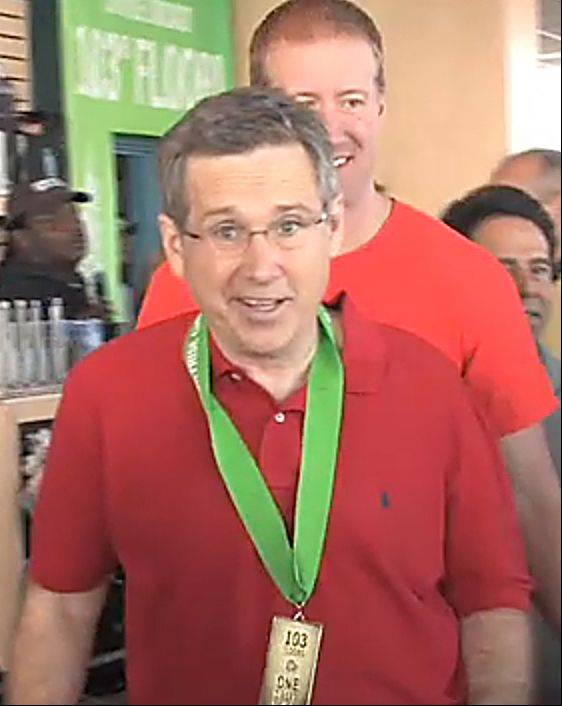Sen. Mark Kirk smiles with his medal as he comes out of the stairwell on the 103rd floor of the Willis Tower during a benefit climb Sunday for the Rehabilitation Institute of Chicago. Kirk has been recovering from a stroke and working with RIC physical therapist Michael Klonowski, background.