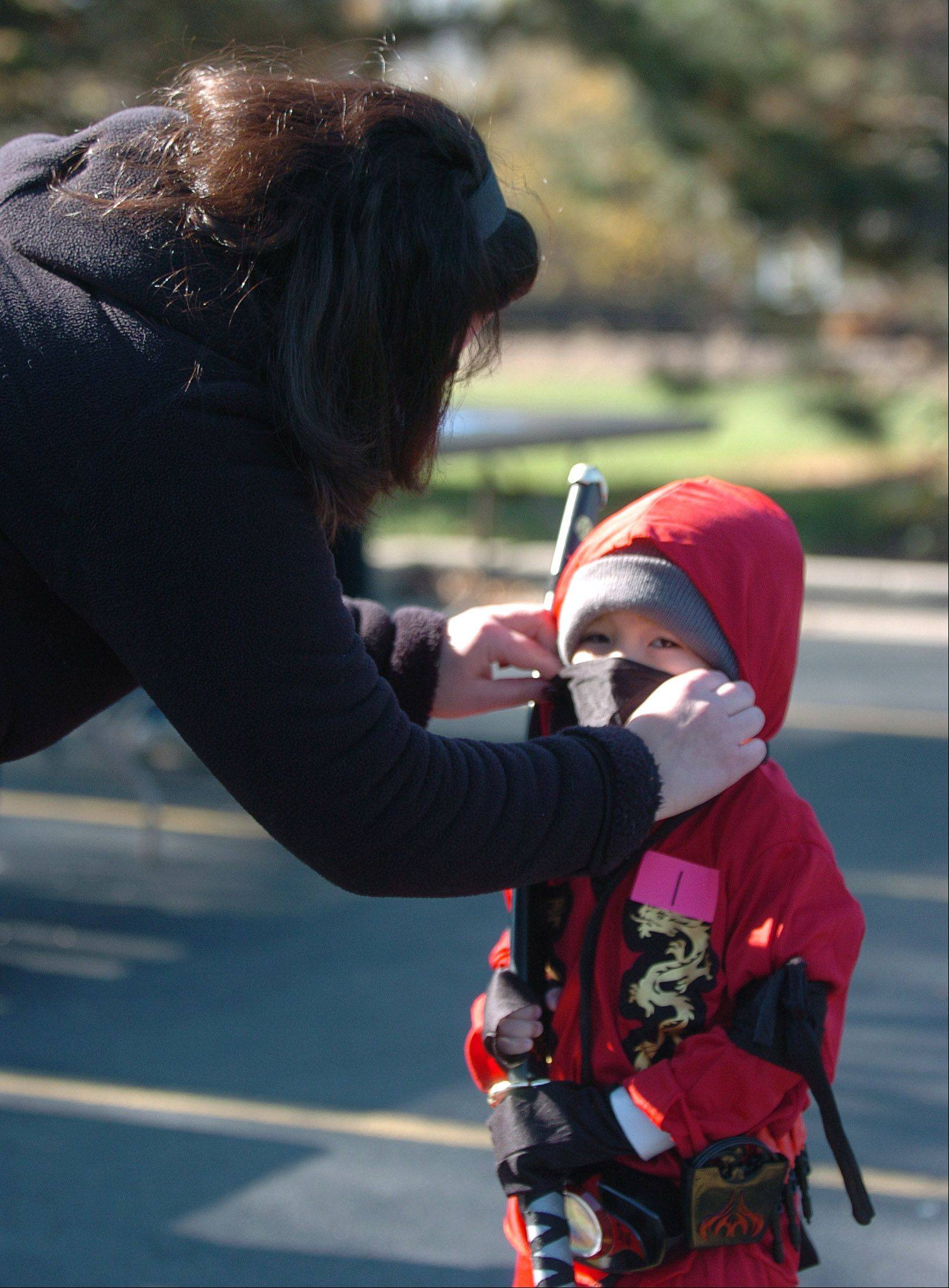 Kim Engel of Wheaton helps Oscar Smith, 5, of West Chicago get his face mask on during the West Chicago's Park District's Halloween Parade and costume contest at West Chicago Library Saturday. Kim is Oscar's big sister.