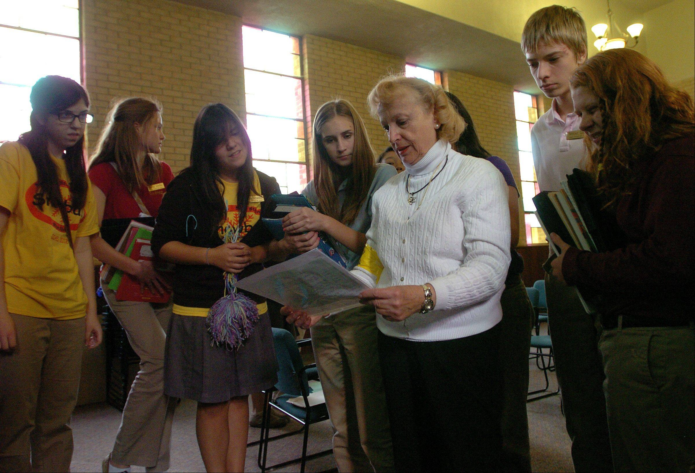 "Holocaust survivor Ida Kersz of Skokie shows pictures of her family while talking about her experiences to Carmel Catholic High School students as part of a class titled, ""the Holocaust and Genocide in The Modern World."""