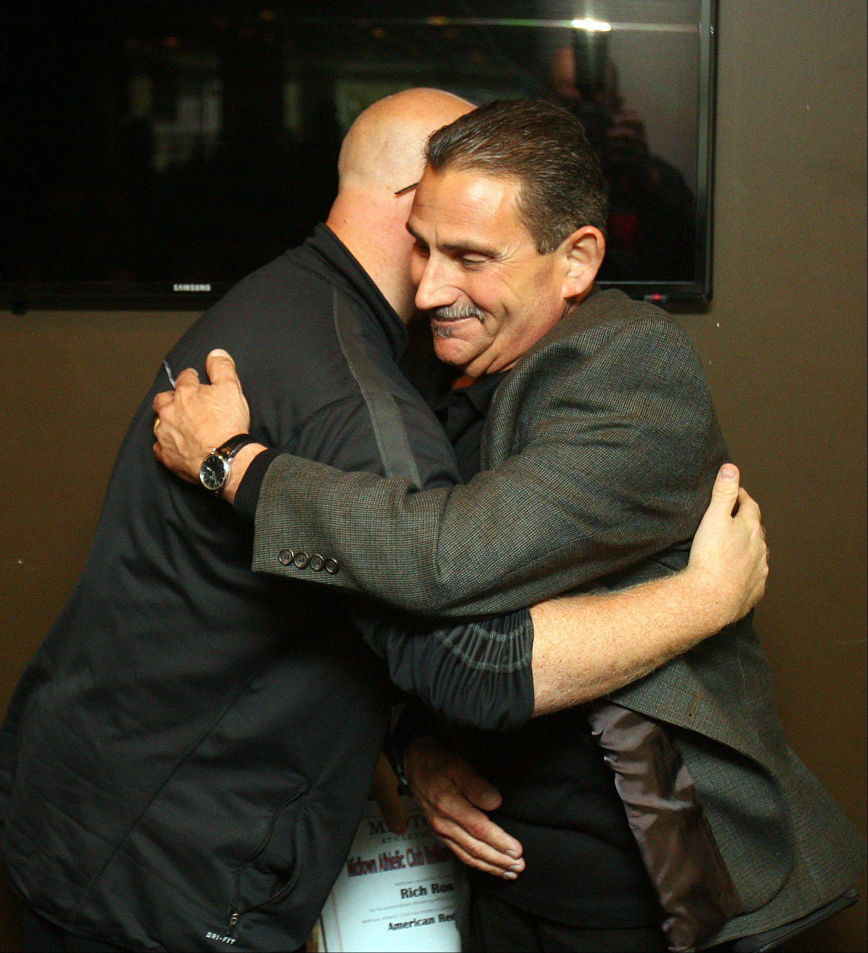 Gary Greenberg of Highland Park hugs Midtown Athletic Club personal trainer Rich Rossi during a ceremony at the facility in Bannockburn Thursday. Rossi was honored for saving Greenberg after he suffered a heart attack. Rossi used a AED (Automated External Defibrillator) to save his life.