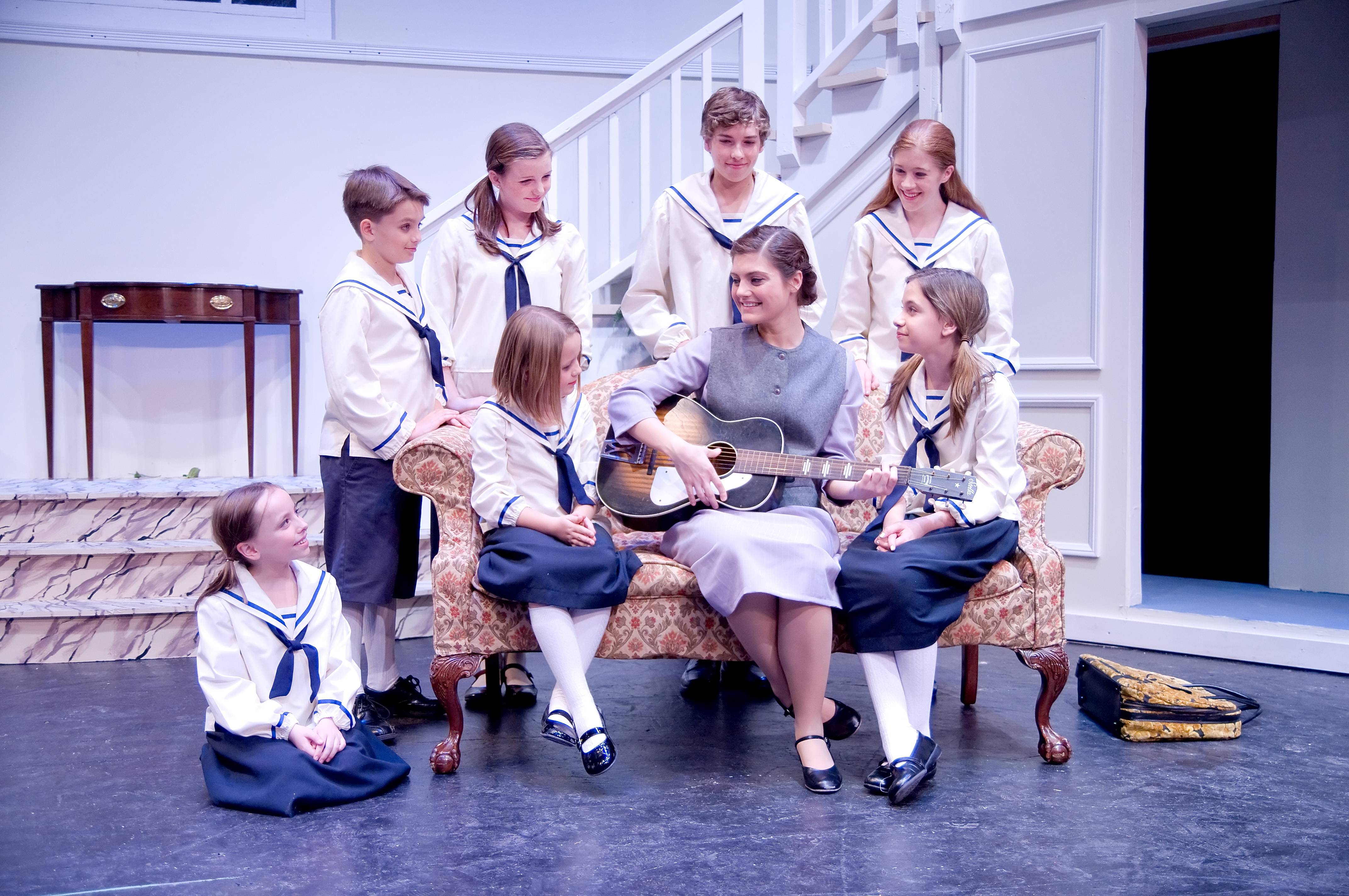 "Maria (Rachelle Kates, center) sings to the von Trapp children (L-R Alexandra Burkhardt, Gwen Royle, Brock Royle, Anna Chase Lanier, Daniel Flage, Teagan Earley, Tyler Berger) in Wheaton Drama's production of ""The Sound of Music""."