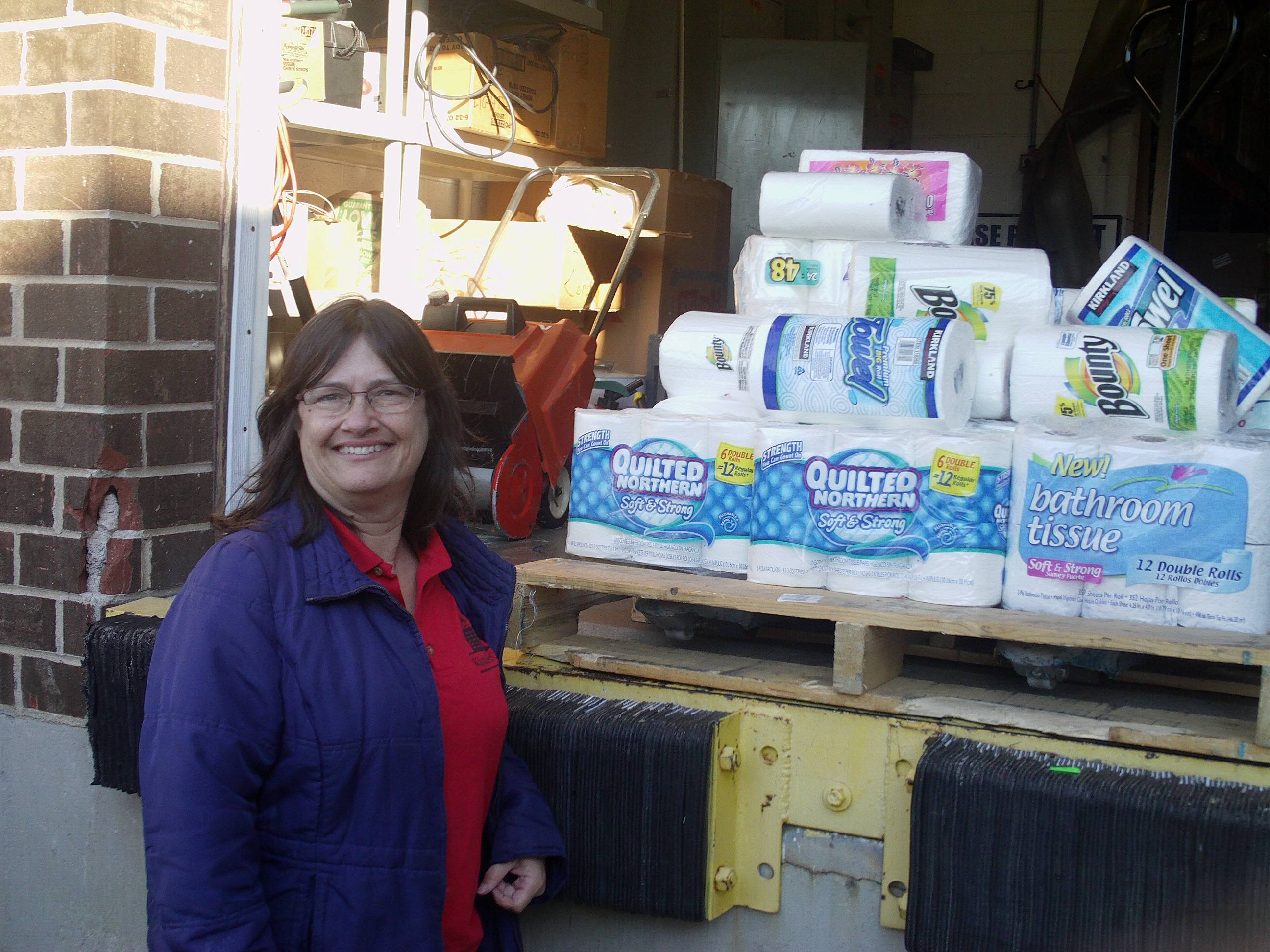 Staff member from Roselle Kindercare poses with donated paper products for needy seniors.