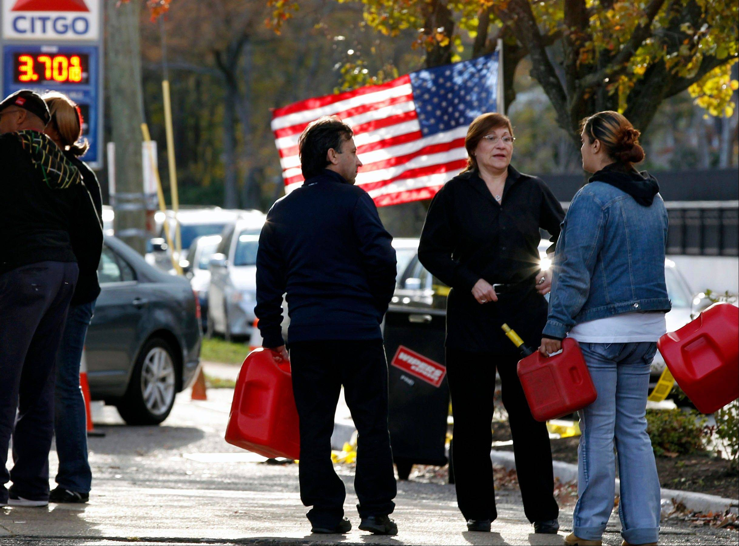 People wait in line with containers to purchase gasoline at filling station in Metuchen, N.J.