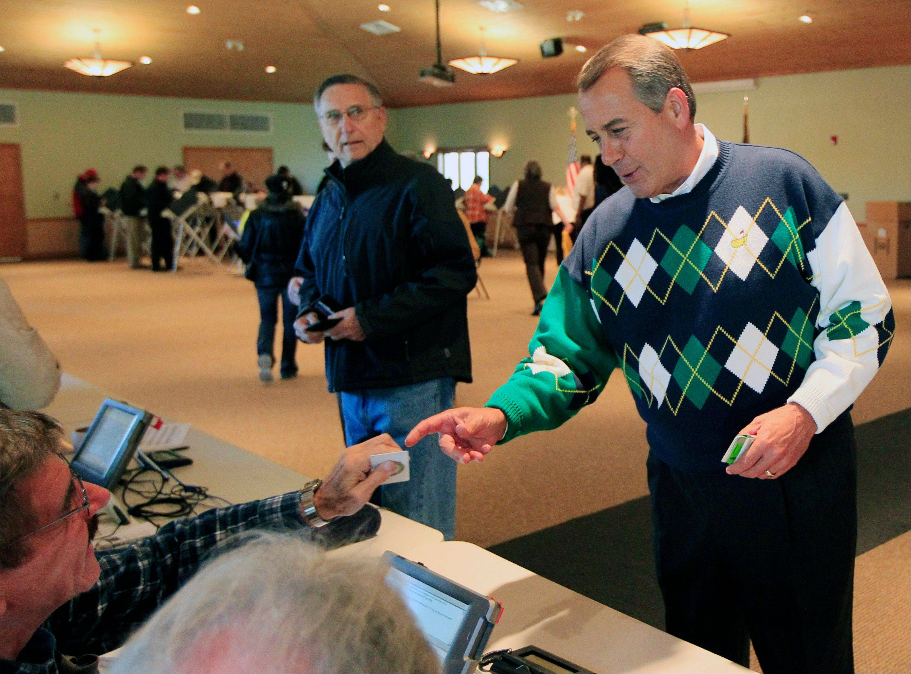 Speaker John Boehner, R-Ohio, presents a photo id as he gets his ballot to vote, Tuesday, Nov. 6, 2012, at Ronald Reagan Lodge in West Chester, Ohio. After a grinding presidential campaign, Americans head into polling places across the country.