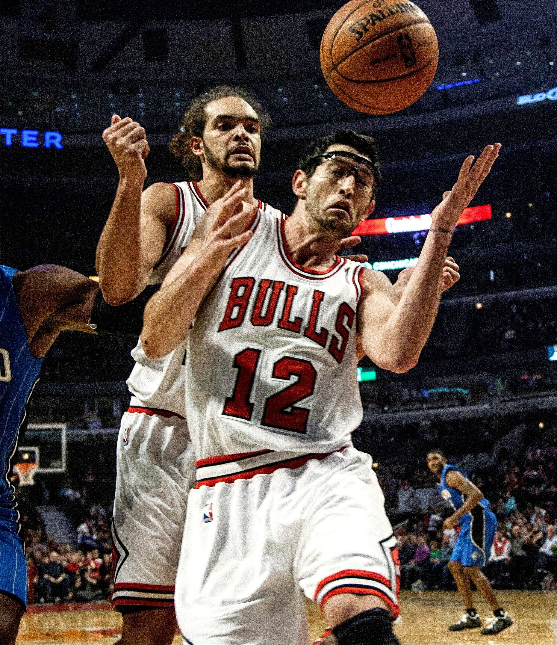 Kirk Hinrich (12) and Joakim Noah try to save the ball from going out of bounds during the first quarter of the Bulls� win Tuesday night at the United Center.