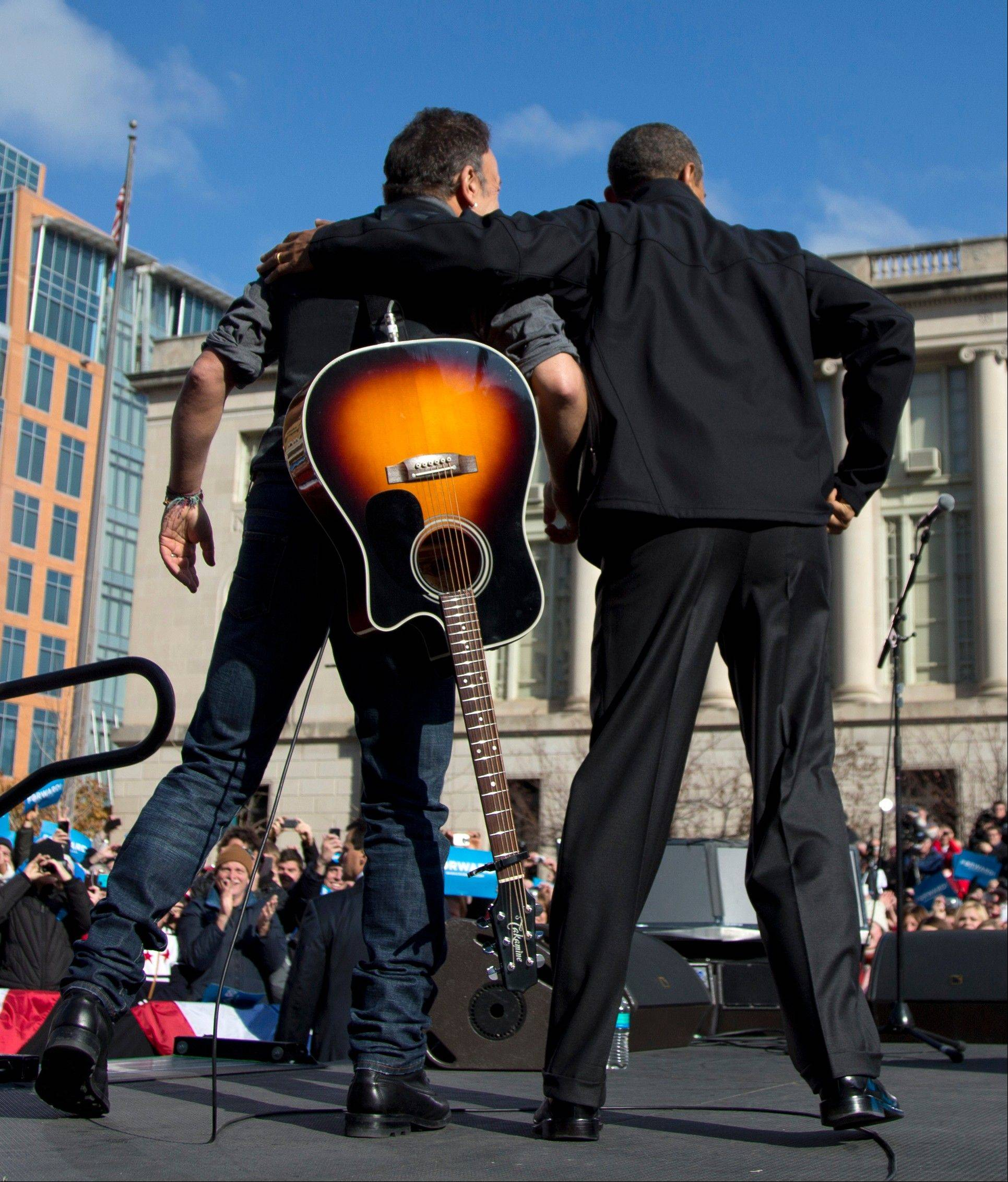 President Barack Obama and singer Bruce Springsteen stand together onstage during a campaign event Monday in Madison, Wis.